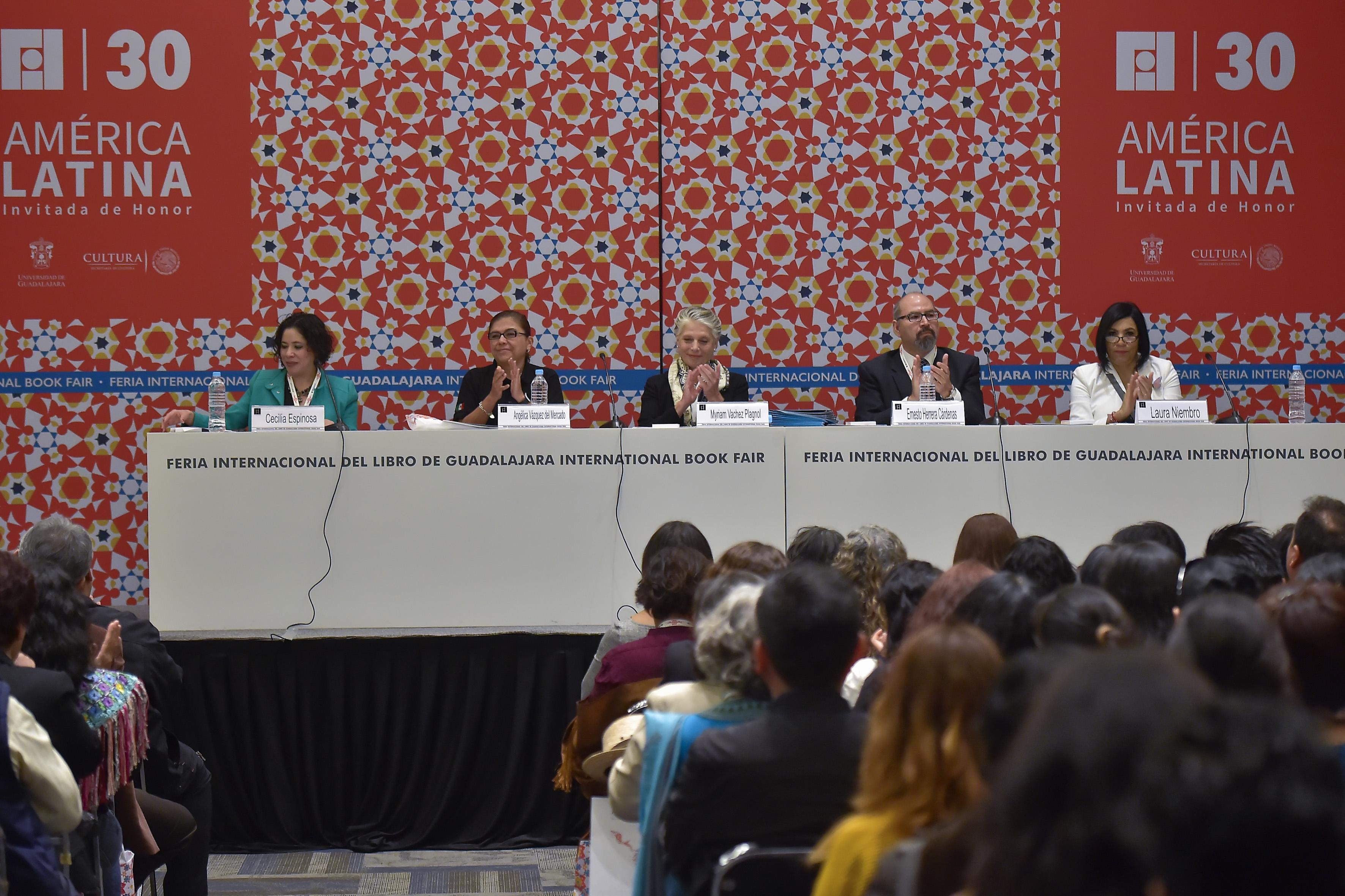 Miembros panelistas participantes en ceremonia de premiación, aplaudiendo.