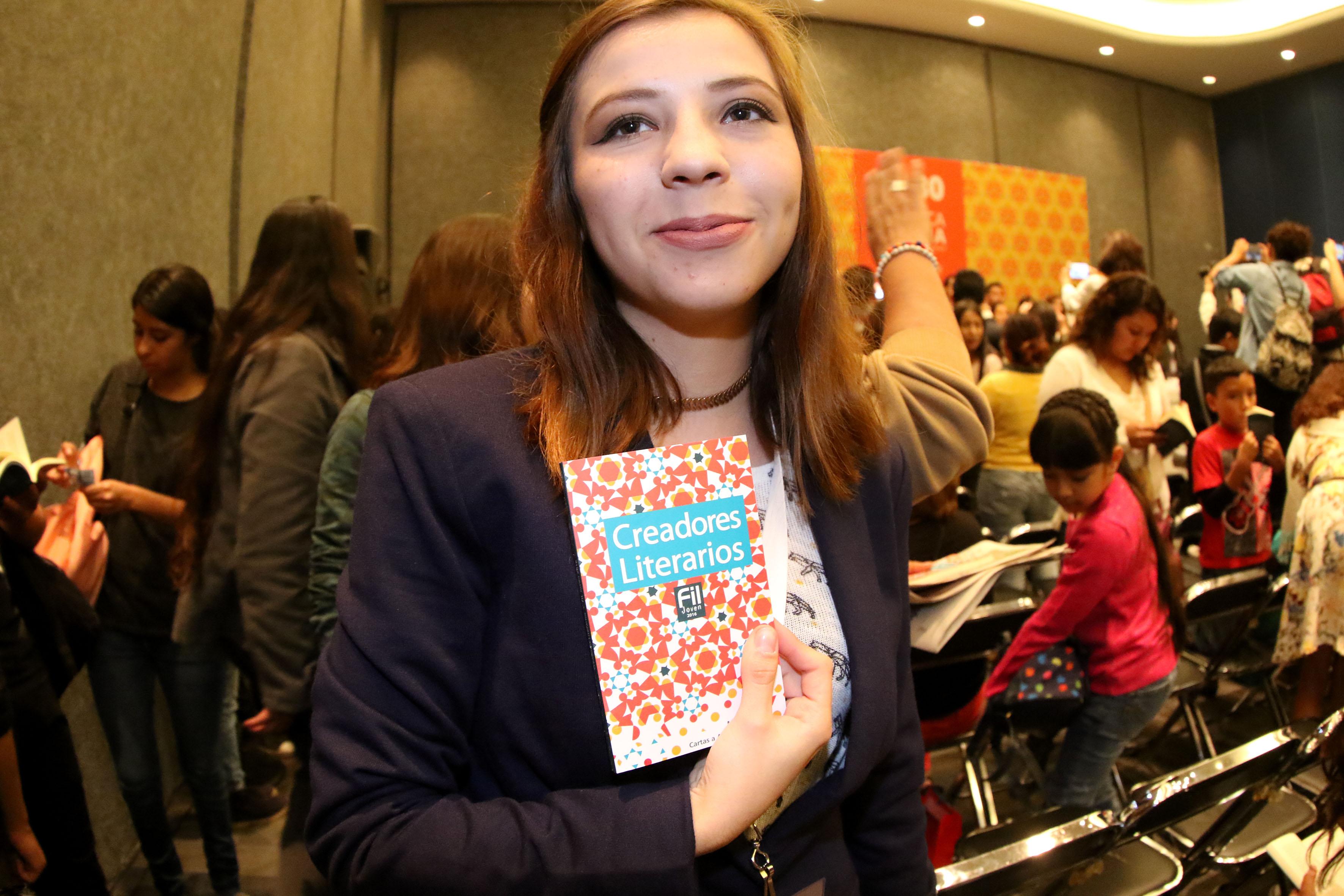 """Estudiante ganadora del concurso """"Creadores Literarios FIL Joven"""", mostrando el libro editado en la que se presenta las obras de los ganadores."""