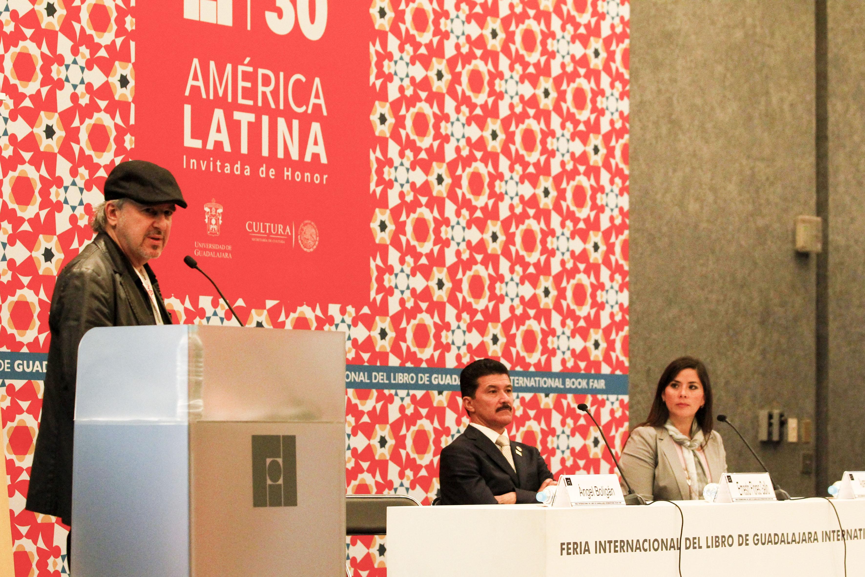 El caricaturista cubano Ángel Boligán, con micrófono en podium del evento, haciendo uso de la palabra.