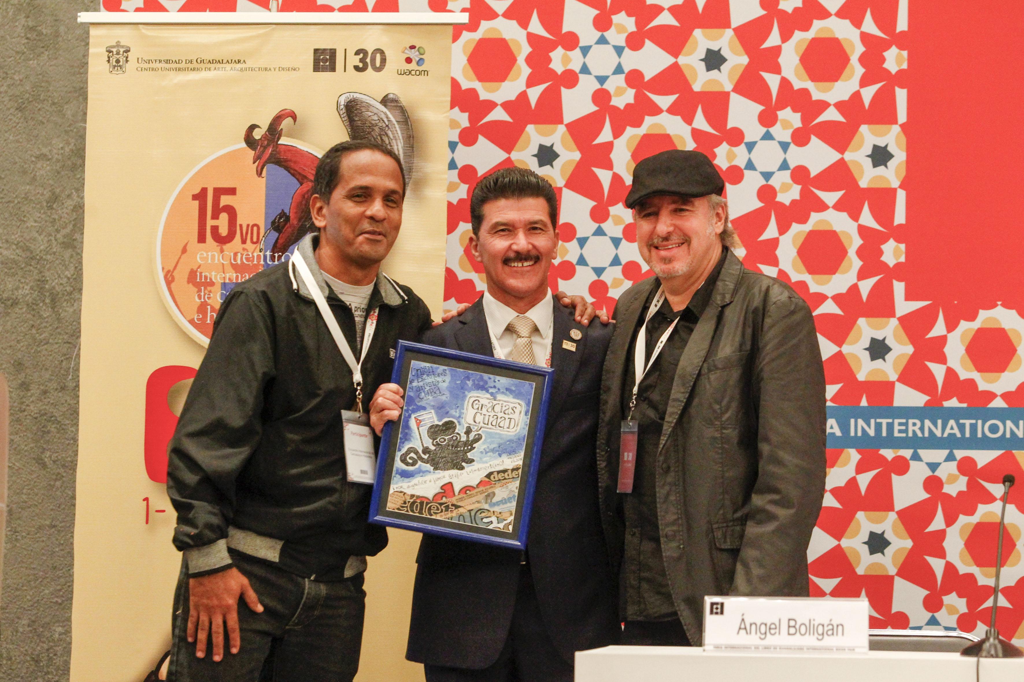 El Rector del CUAAD, maestro Ernesto Flores Gallo, mostrando un reconocimiento con motivo de los 15 años del encuentro.