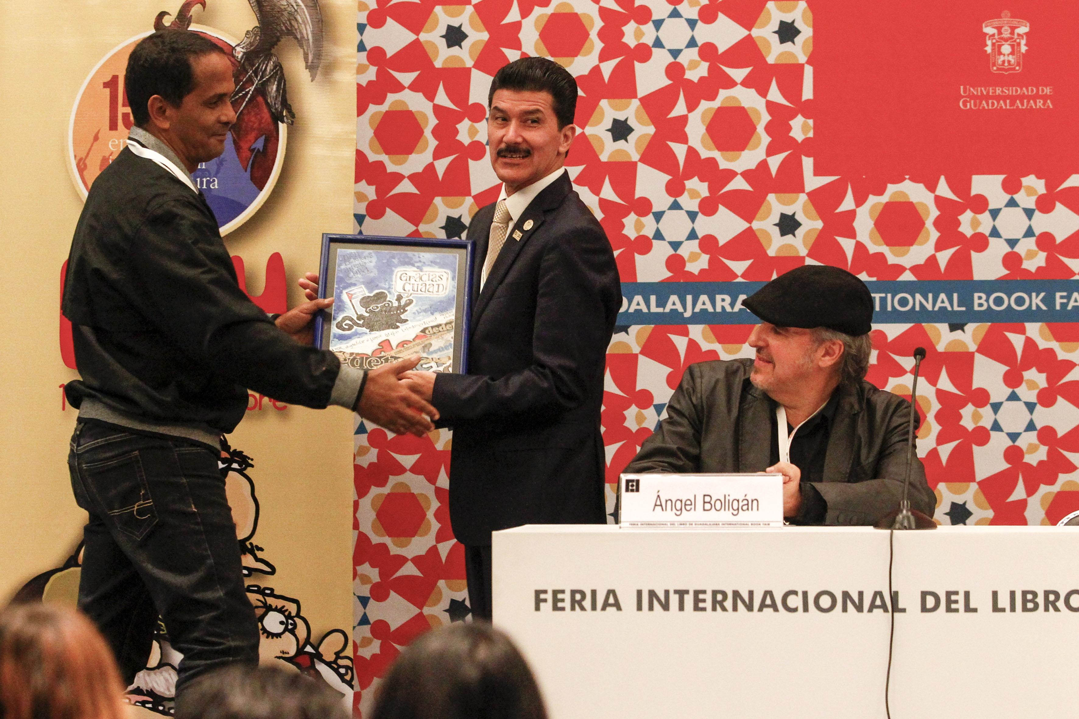 Adán Iglesias Toledo, entregando reconocimiento al Rector del CUAAD, maestro Ernesto Flores Gallo, como organizador de los 15 años del encuentro.