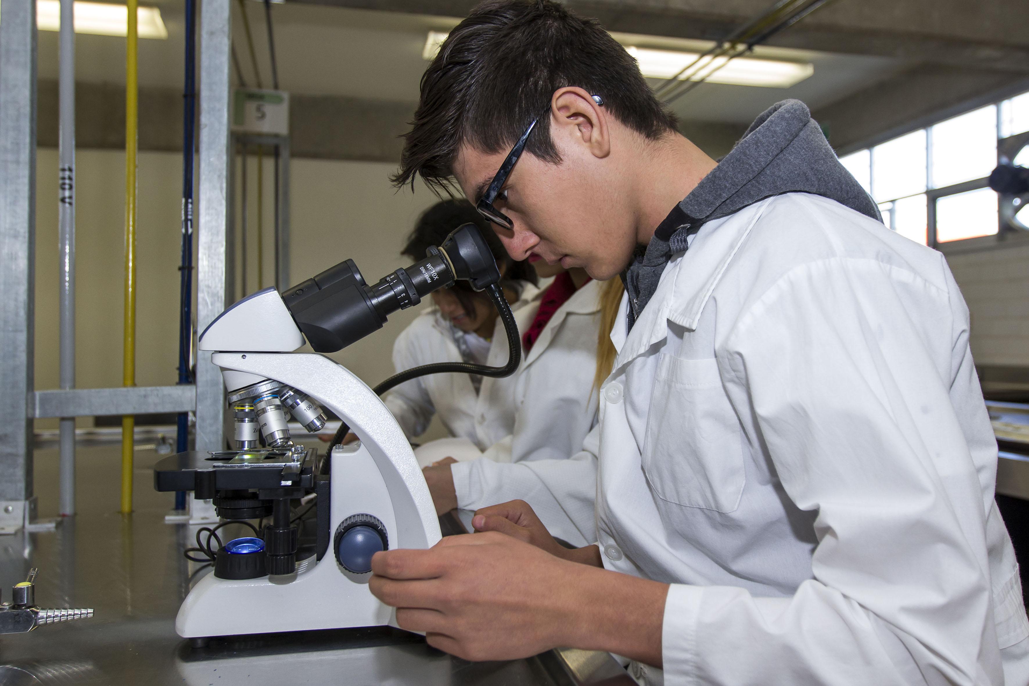 Alumno del Bachillerato Tecnológico en Citología e Histología que se imparte en la Preparatoria 11 de la Universidad de Guadalajara (UdeG) viendo en un microscopio