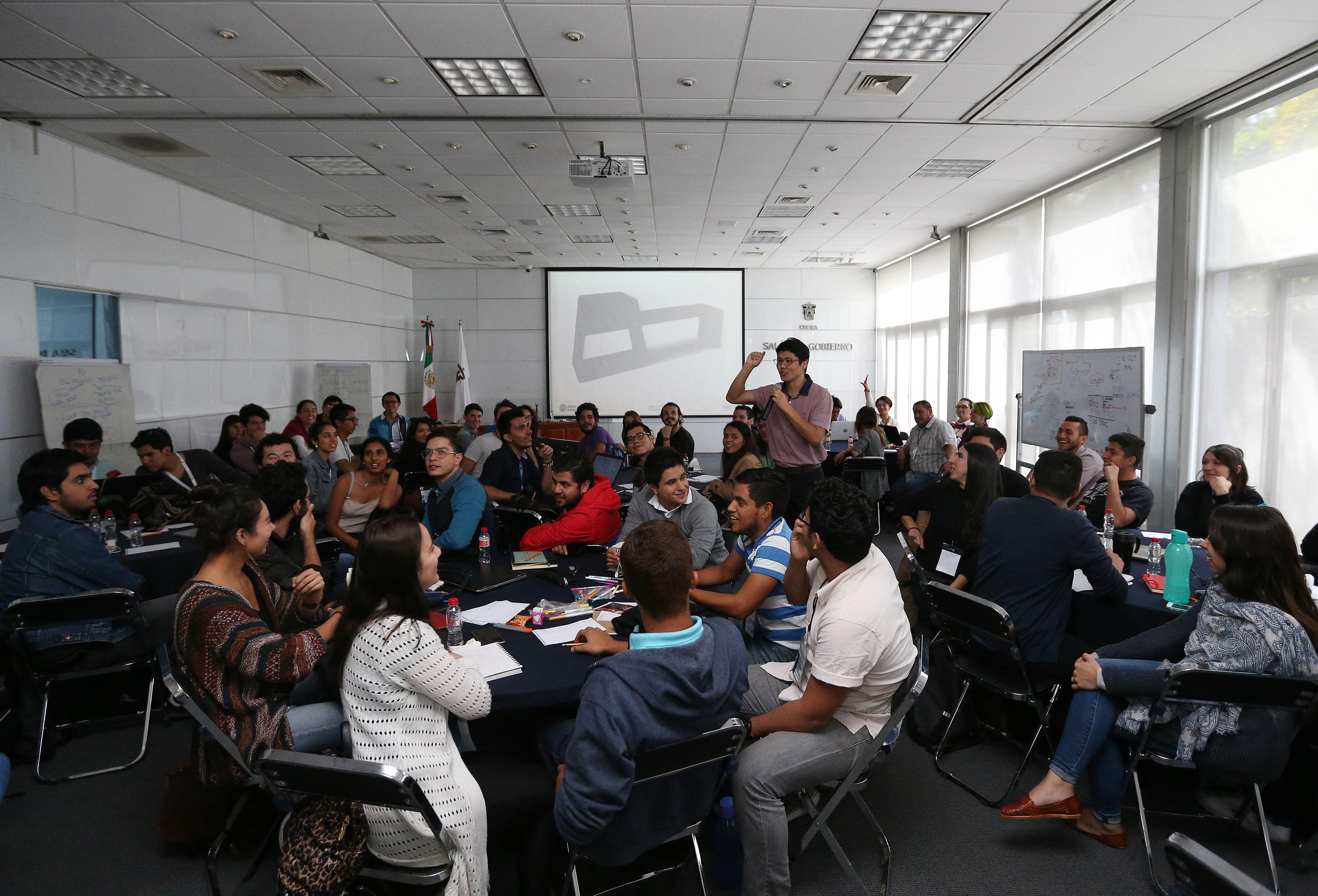 """Estudiantes universitarios asistentes al taller de """"You can innovate"""", con entusiasmo, poniendo atención a su mentor."""