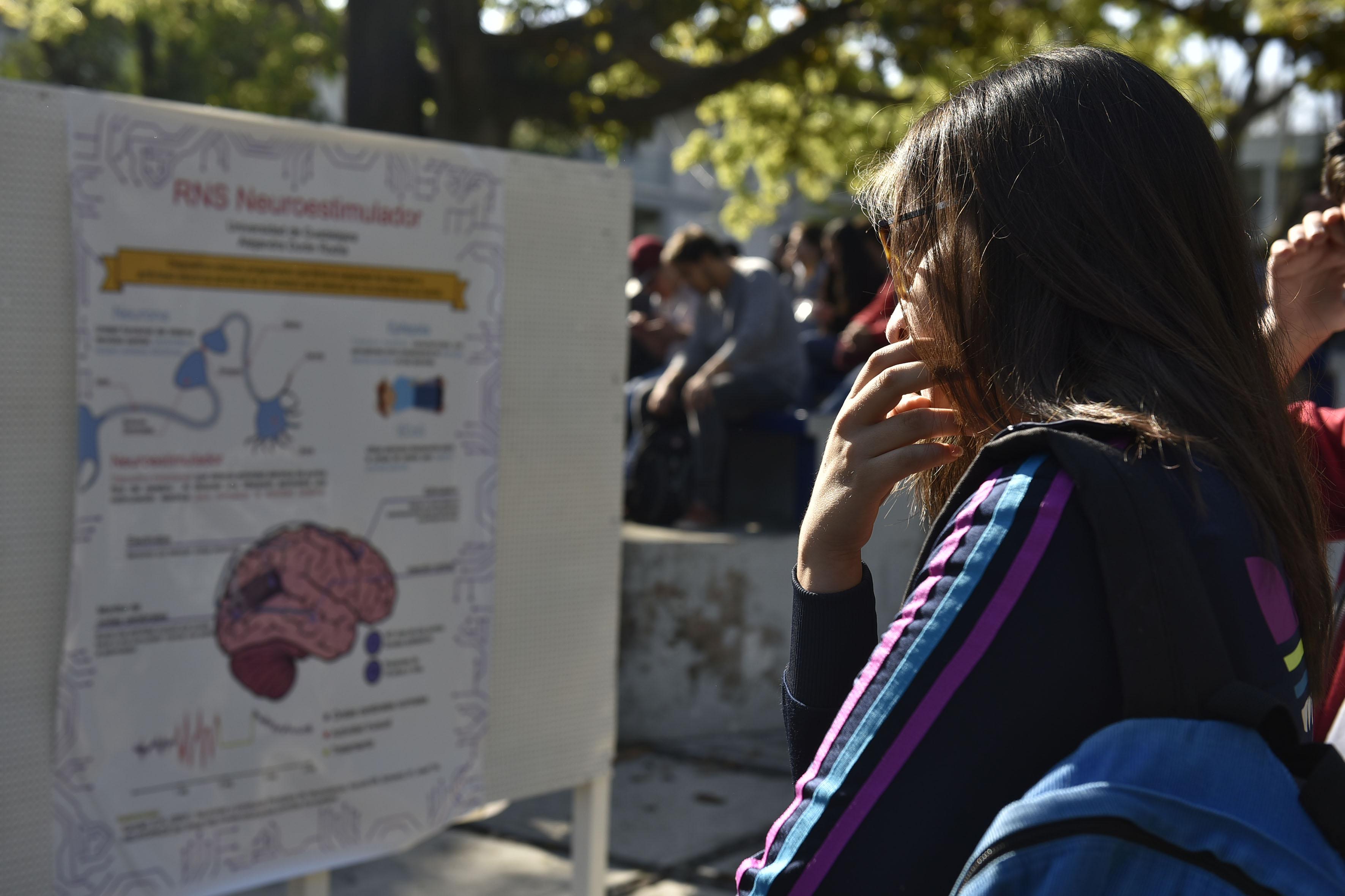 Estudiante del CUCEI observando un cartél de divulgación con referencia al RNS Neuroestimulador.