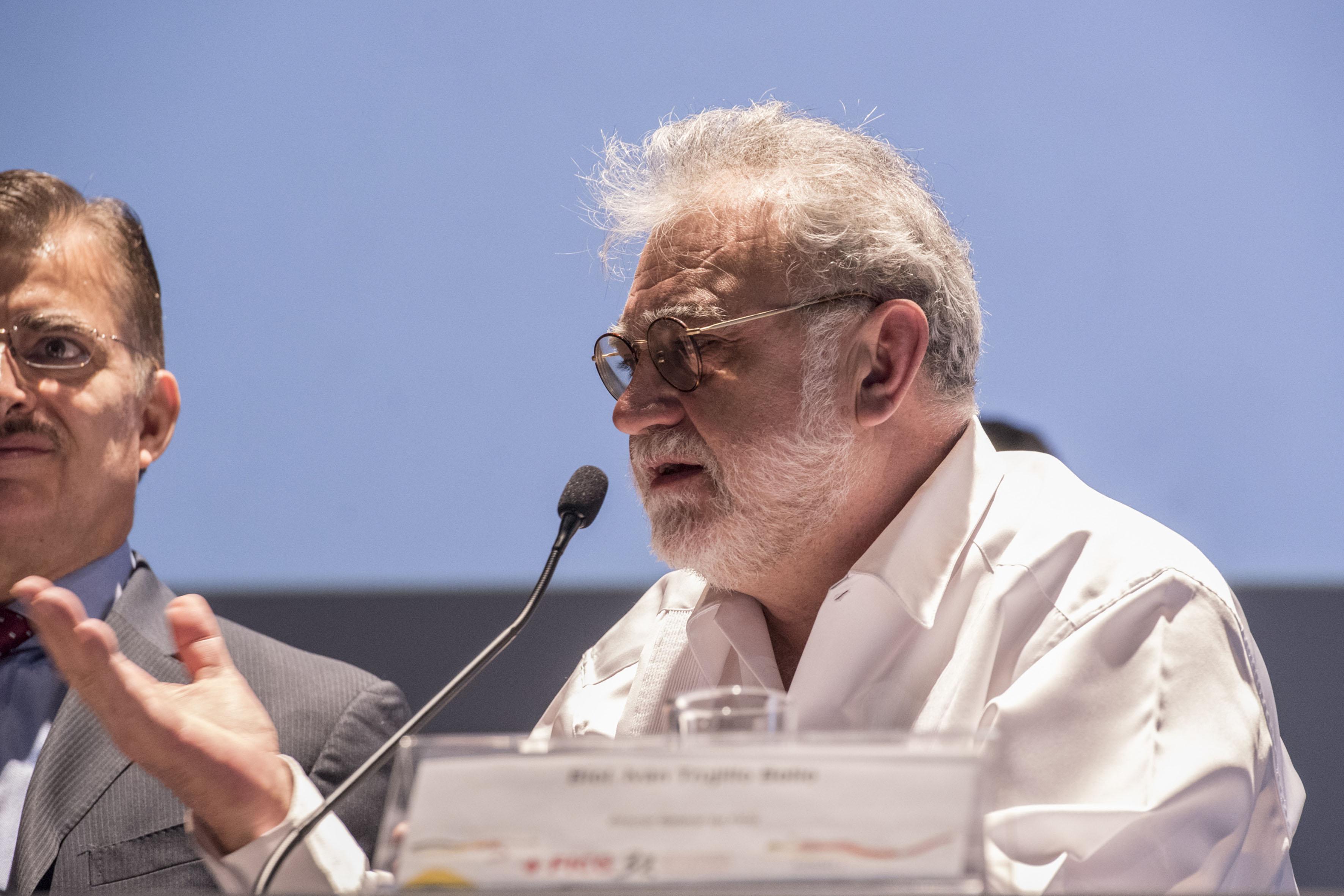 El presidente general de la FICG, el biólogo Iván Trujillo Bolio; con micrófono en mesa del panel, haciendo uso de la palabra.