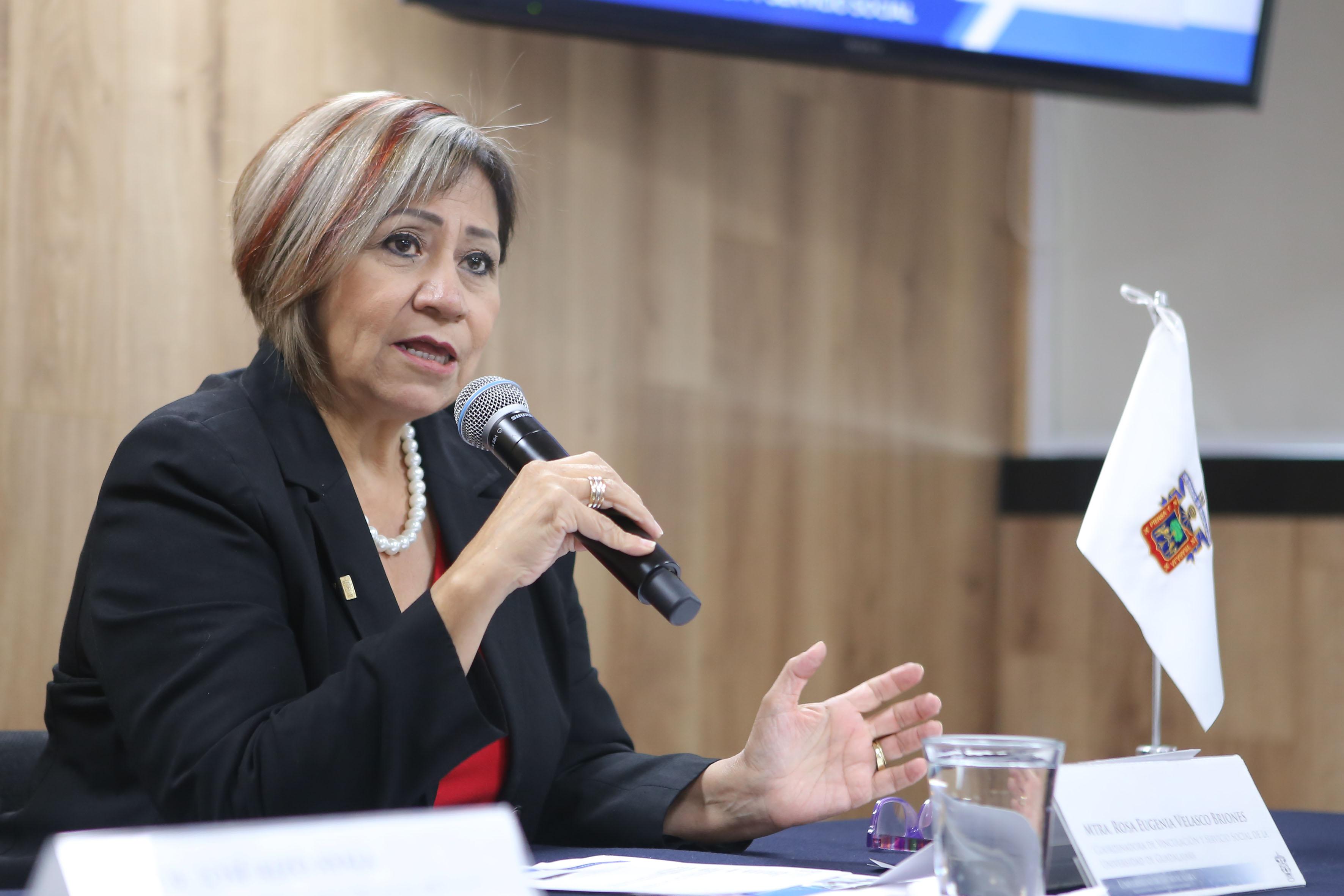 Maestra Rosa Eugenia Velasco Briones, titular de la Coordinación de Vinculación de Servicio Social (CVSS), frente al micrófono.