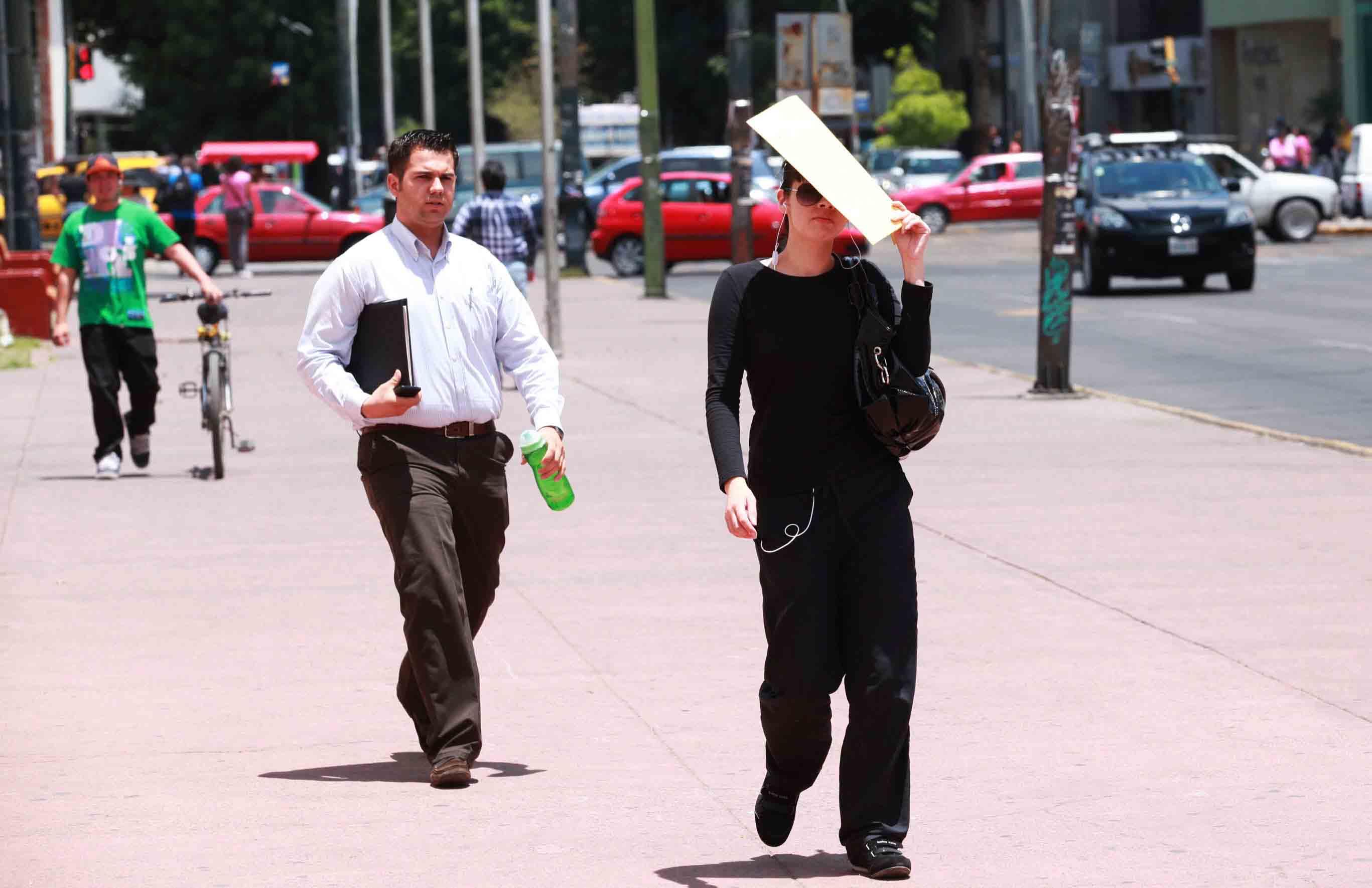 Personas caminando por la calle, portando una botella de agua o cubriéndose con algún objeto del sol, ante las temperaturas cálidas.