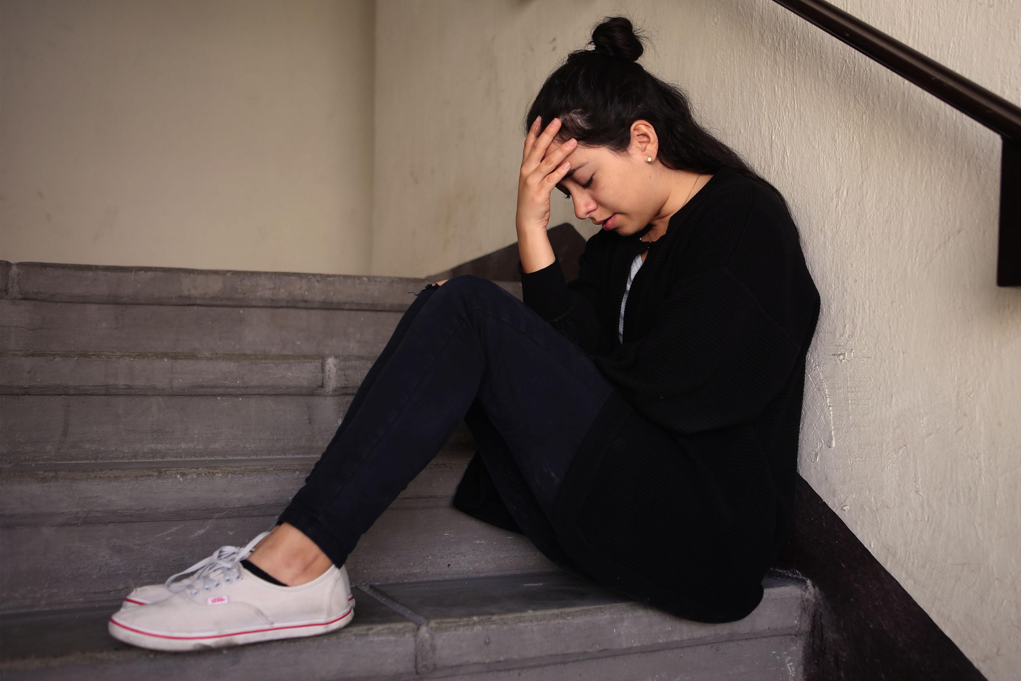 Joven mujer sentada al borde de unas escaleras en posición fetal, con los ojos cerrados,apoyándose con una de las manos, la cabeza.
