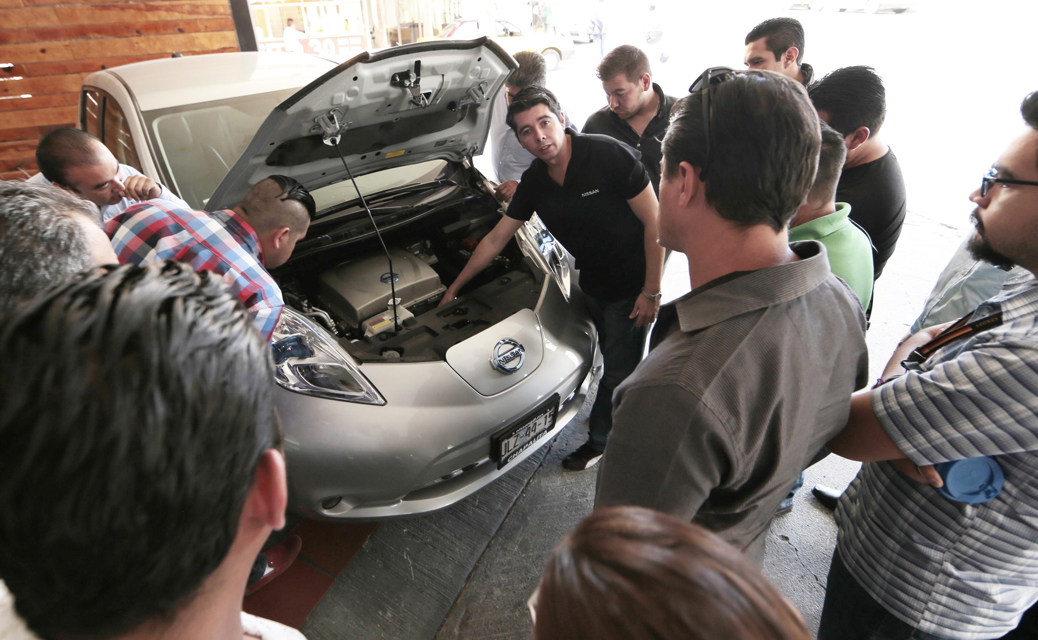 Piloto de la Nissan, experto en el modelo Leaf; explicando el mecanismo de funcionamiento de sus vehículos eléctricos, mientras muestra las partes internas del mismo.