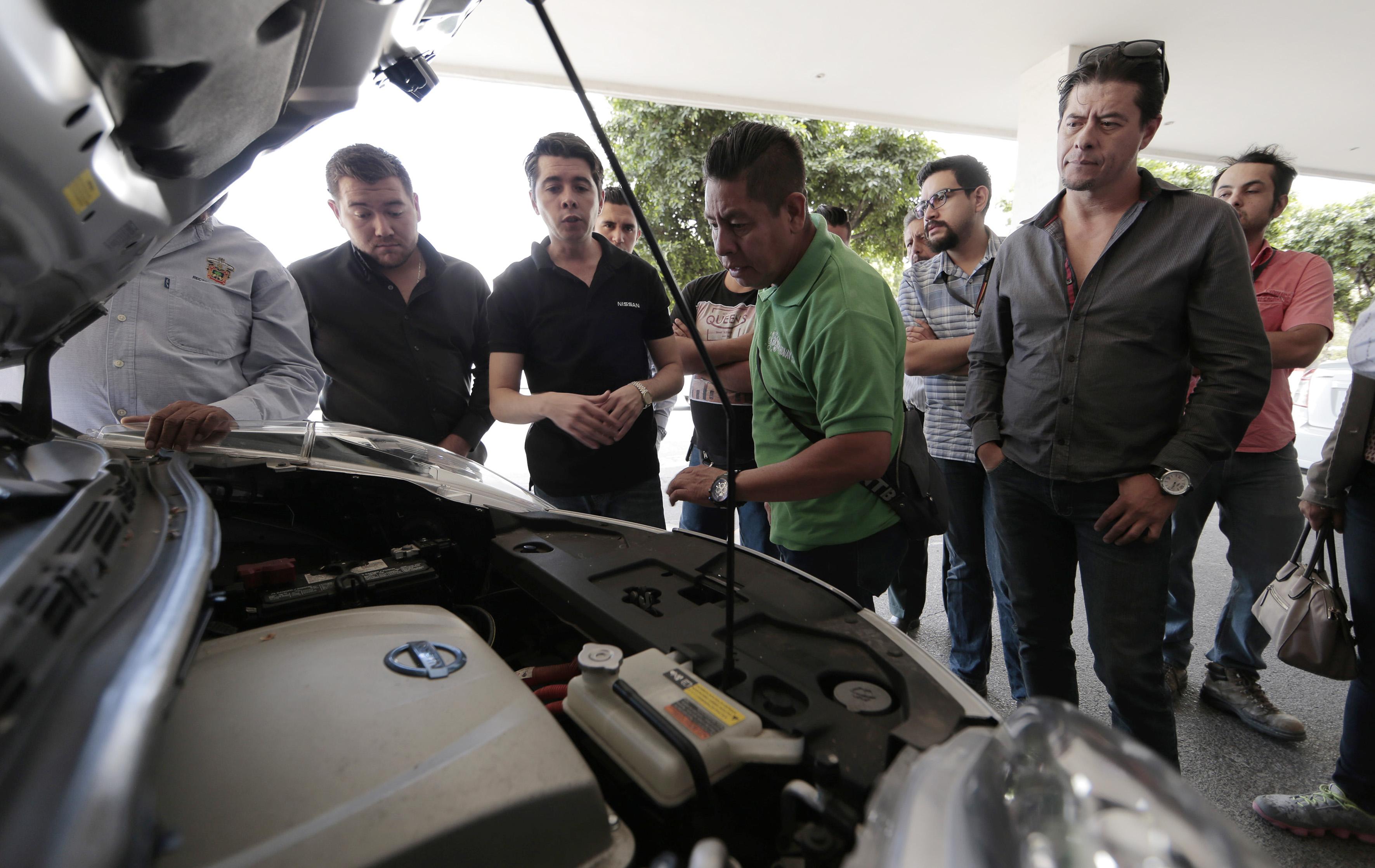 Personal de la empresa Nissan mostrando el motor y partes internas de los vehículos eléctricos, como parte de la capacitación a choferes de la Universidad de Guadalajara que los conducirán.