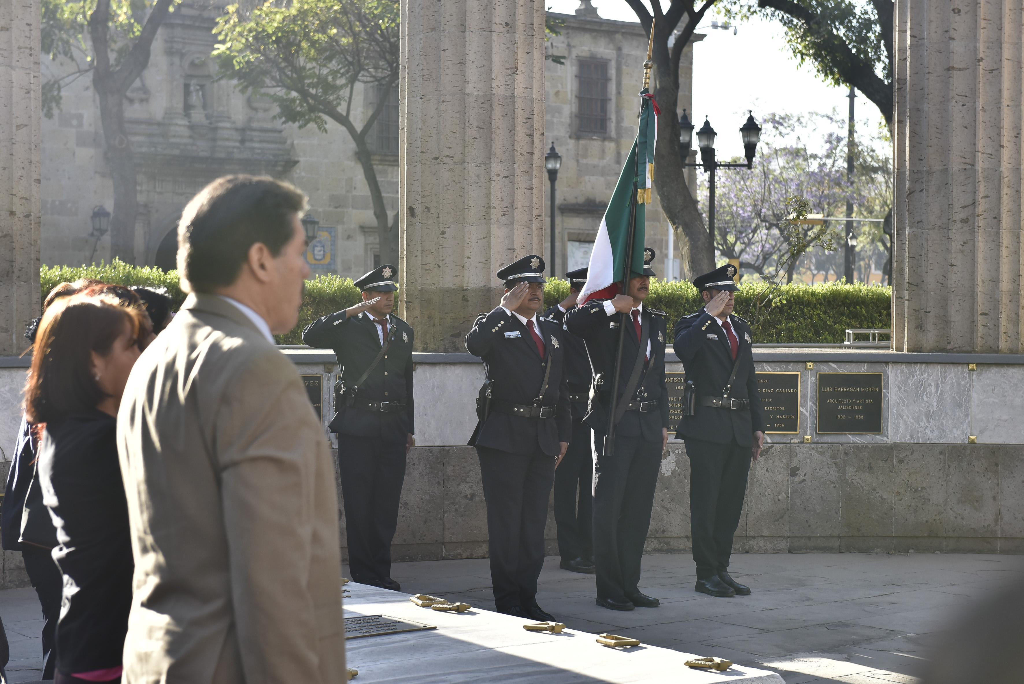 Policías municipales haciendo honores a la bandera en la Rotonda de los Hombres Ilustres, durante conmemoración del 137 aniversario del natalicio de Irene Robledo García.