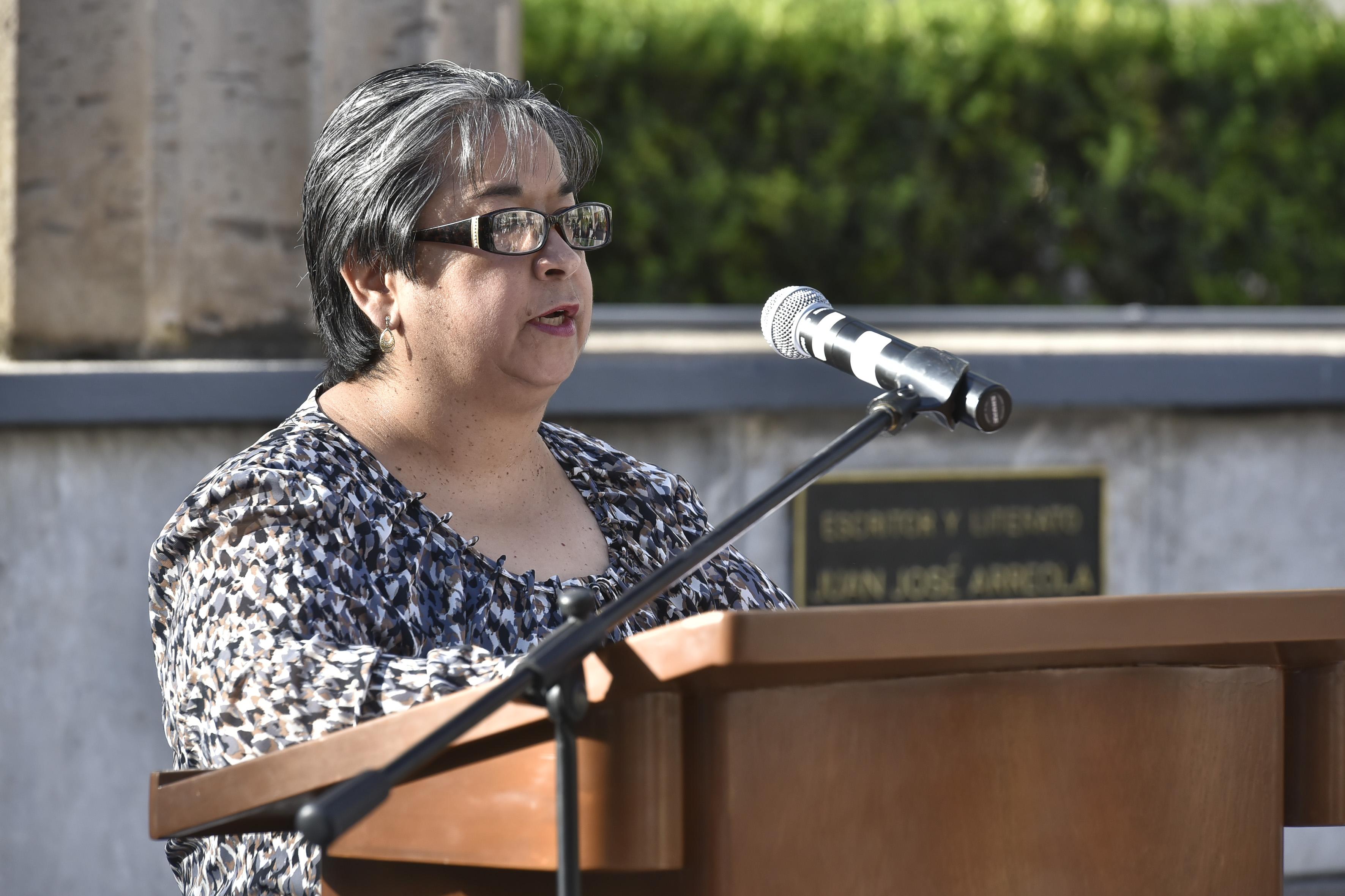 Maestra Adriana Esther Cervantes Carmona, docente del Departamento de Trabajo Social de la Universidad de Guadalajara,haciendo uso de la palabra en podium instalado en la Rotonda de los Hombres Ilustres.