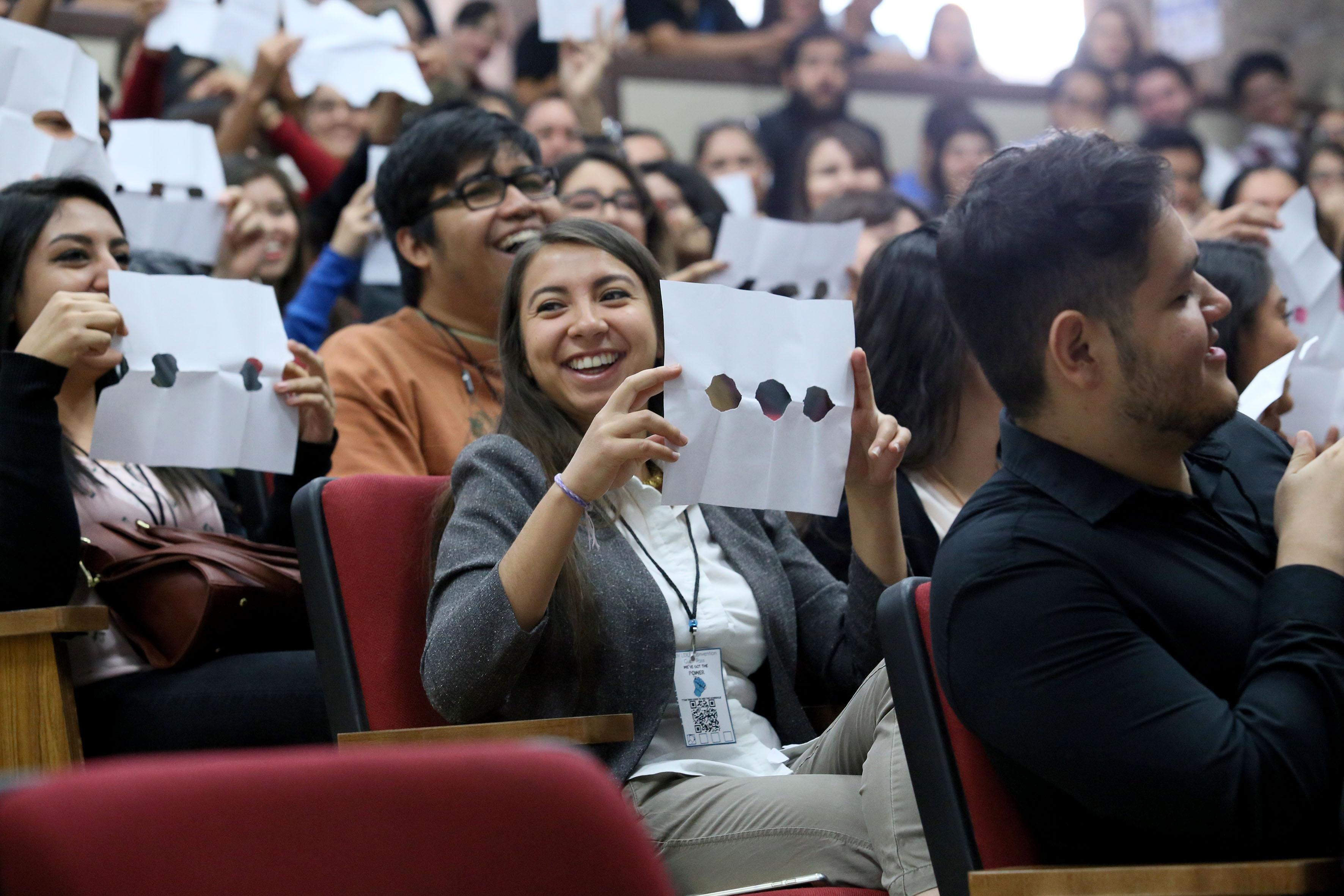 """Estudiantes asistentes a la conferencia """"Shaping tomorrow: new horizons in English language teaching"""", levantando un papel con diversos agujeros, dentro de una interacción sostenida con el conferencista."""