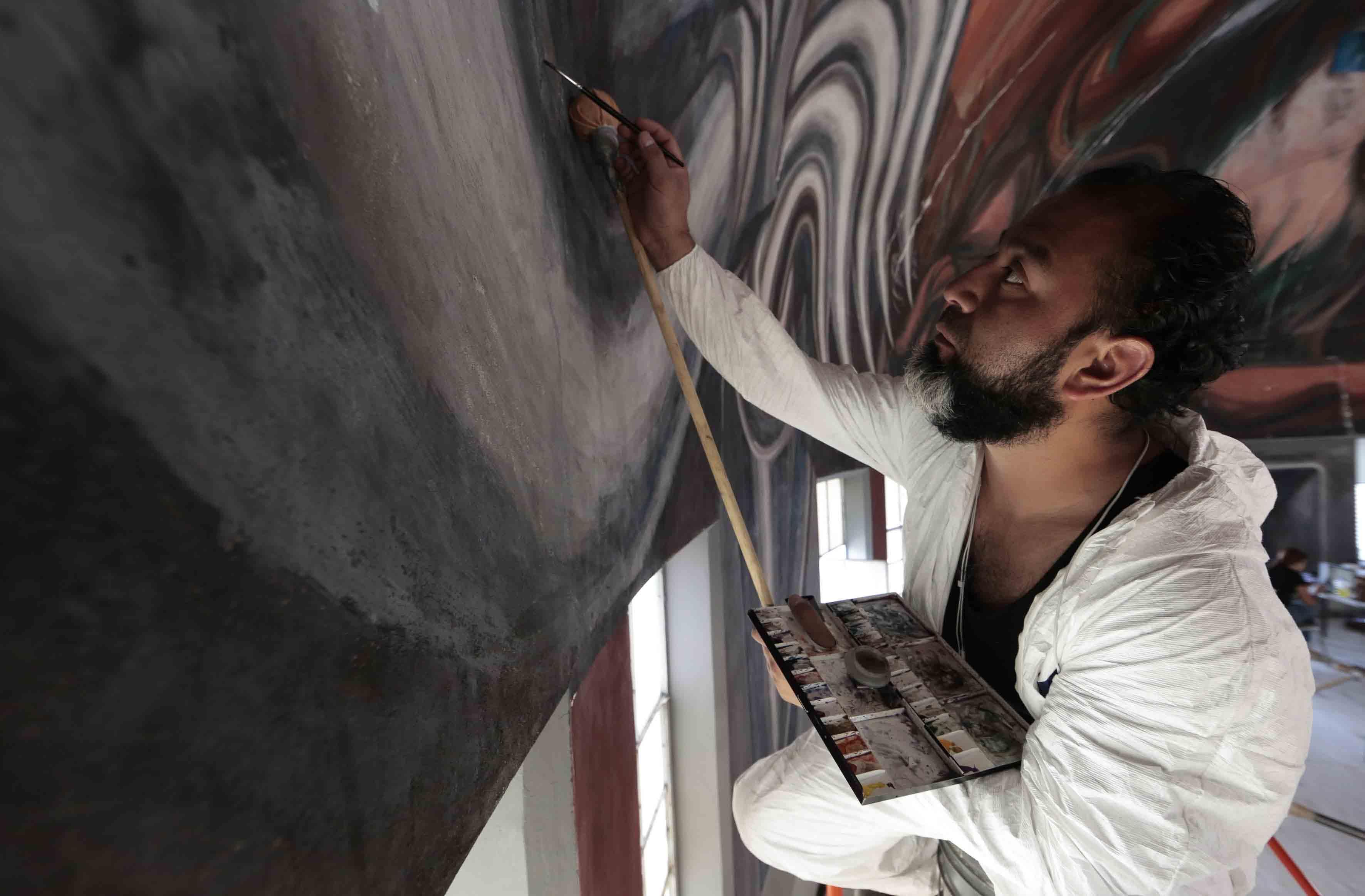 Restaurador trabajando en los murales de José Clemente Orozco en el Paraninfo Enrique Díaz de León de la Universidad de Guadalajara