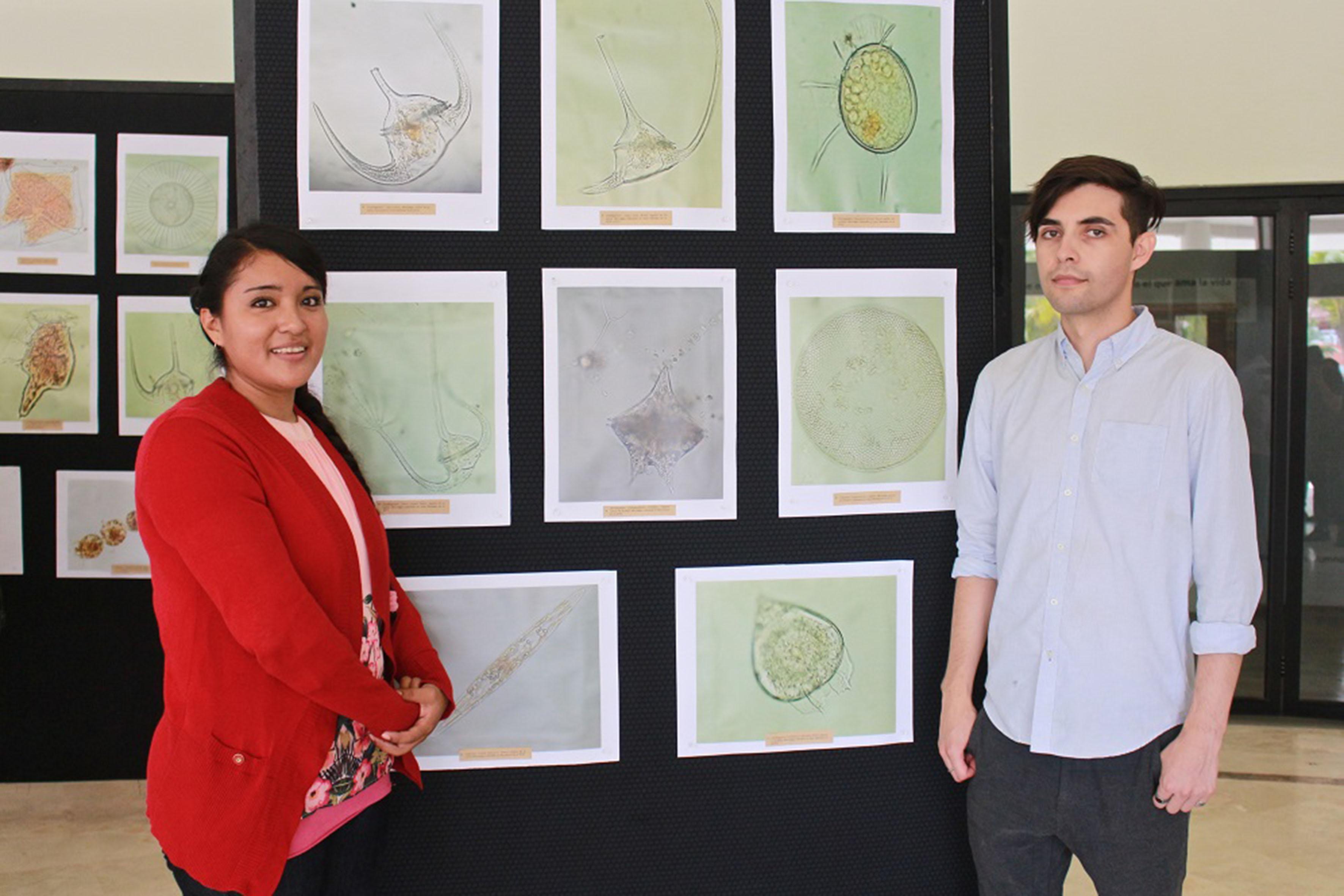 La estudiante de octavo semestre de la licenciatura en Biología, Mayreli Sánchez Dueñas y el egresado de la misma carrera, Nelson Sahagún Uribe, a un lado de su exposición fotográfica de micro algas marinas.