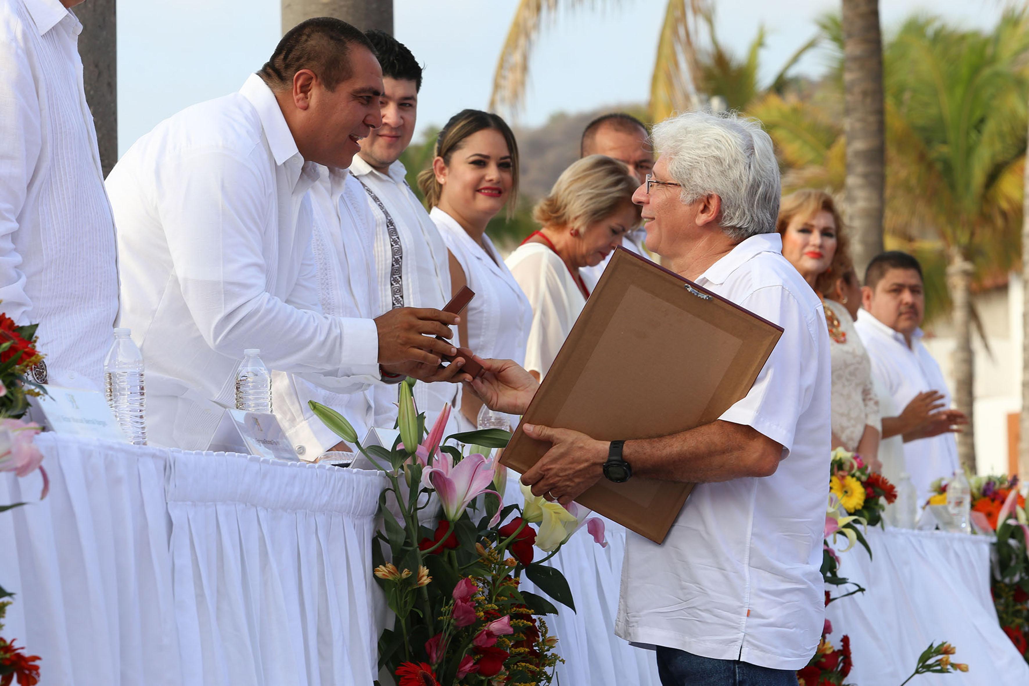 """Doctor Amílcar Levi Cupul Magaña, coordinador del Centro de Investigaciones Costeras (CIC), recibiendo el premio """"Guadalupe Sánchez Torres"""", por haber sobresalido en el cuidado y la conservación del medio ambiente."""