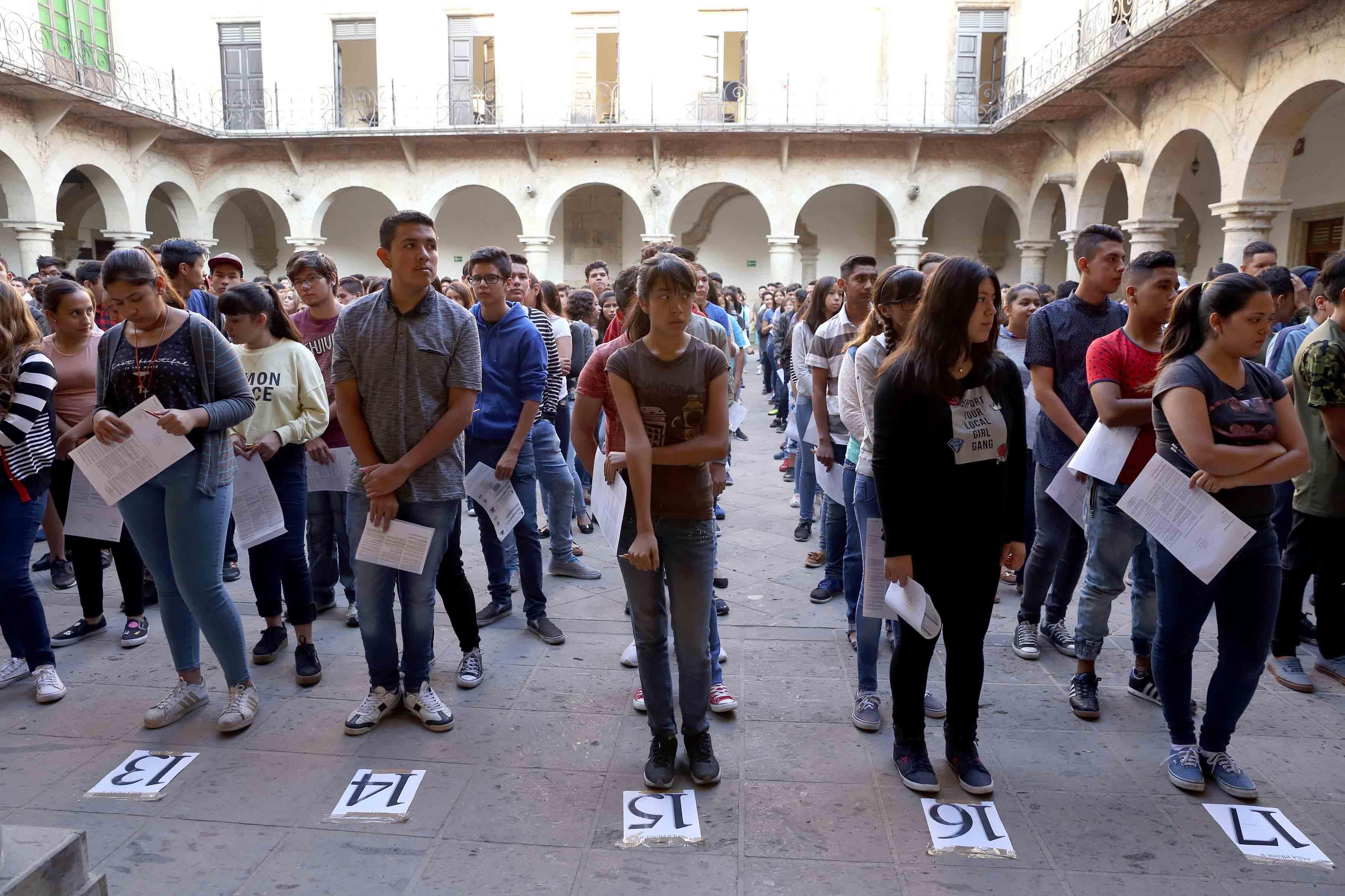 Aspirantes de preparatoria formados en fila con su solicitud para poder entrar a los salones a hacer el examen piense II.