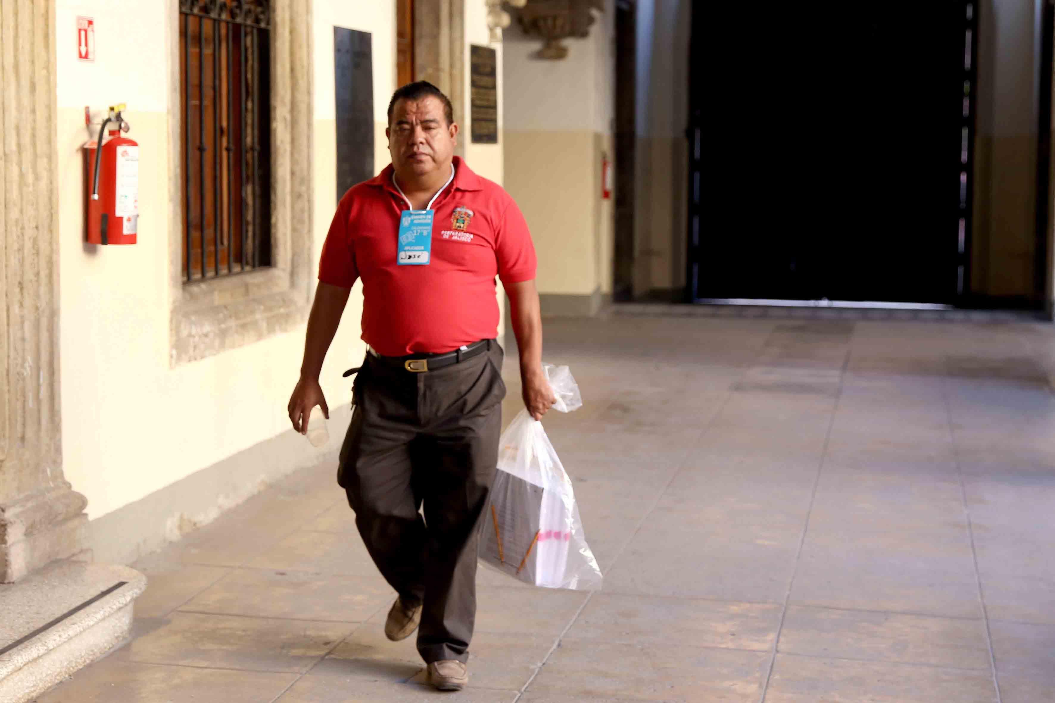 Aplicador pasando por los pasillos de la preparatoria de Jalisco, con el paquete de examenes Piense II.