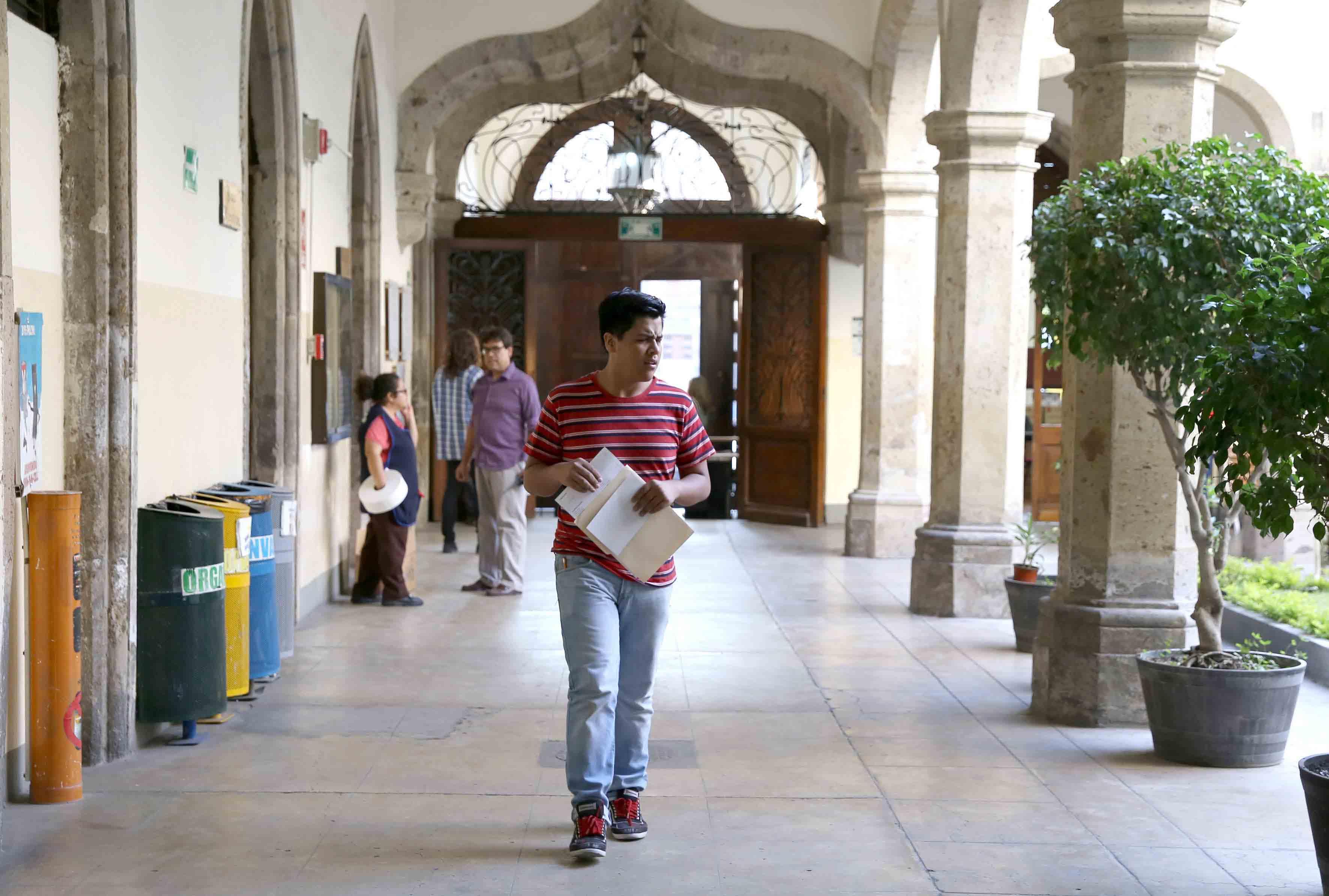 Aspirante a preparatoria, entrando a la preparatoria de Jalisco, con su carpeta de documentos y solicitud para hacer el examen Piense II.