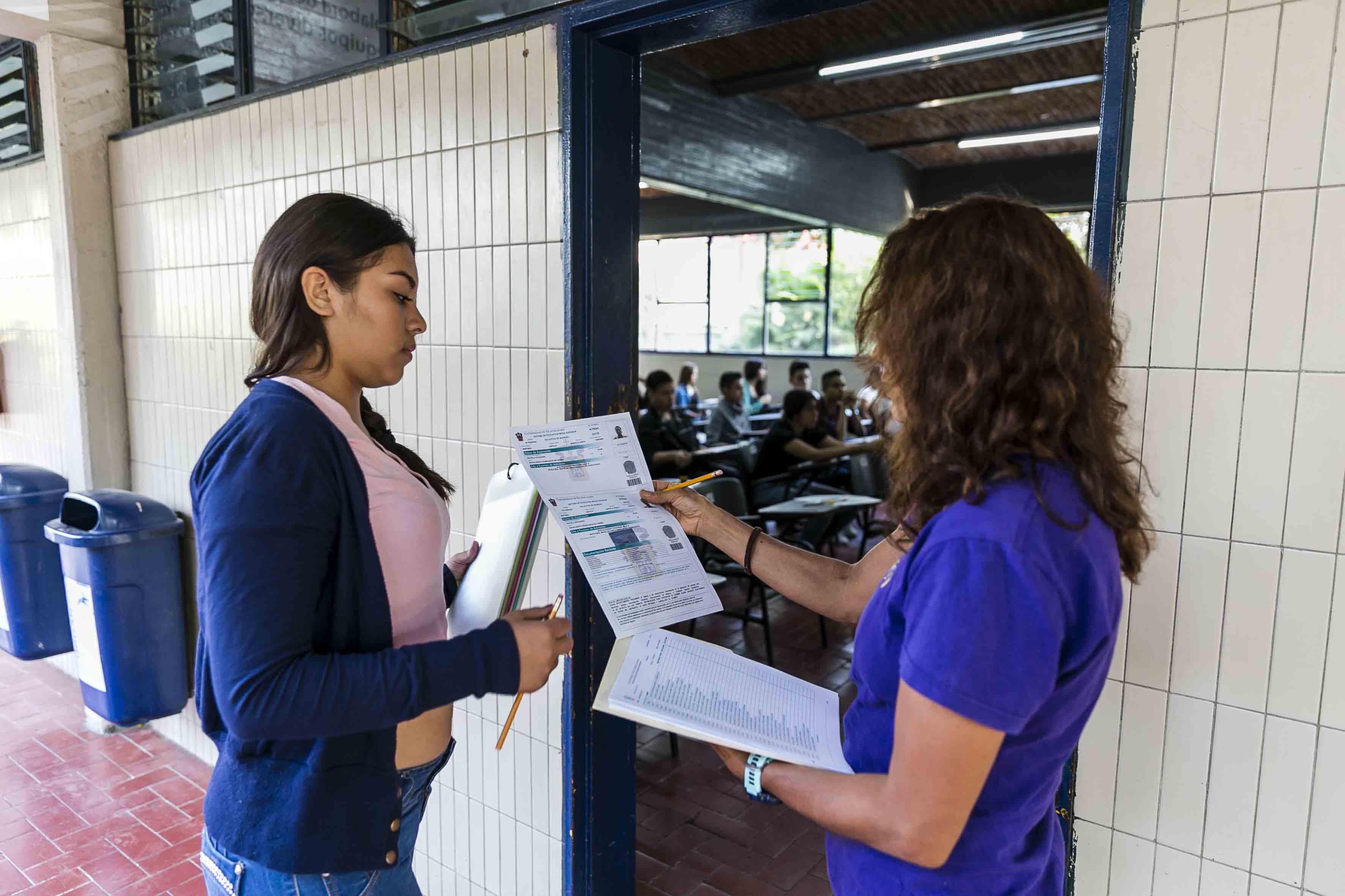 Aplicadora de examen checando la solicitud de aspirante a preparatoria, con su listado.