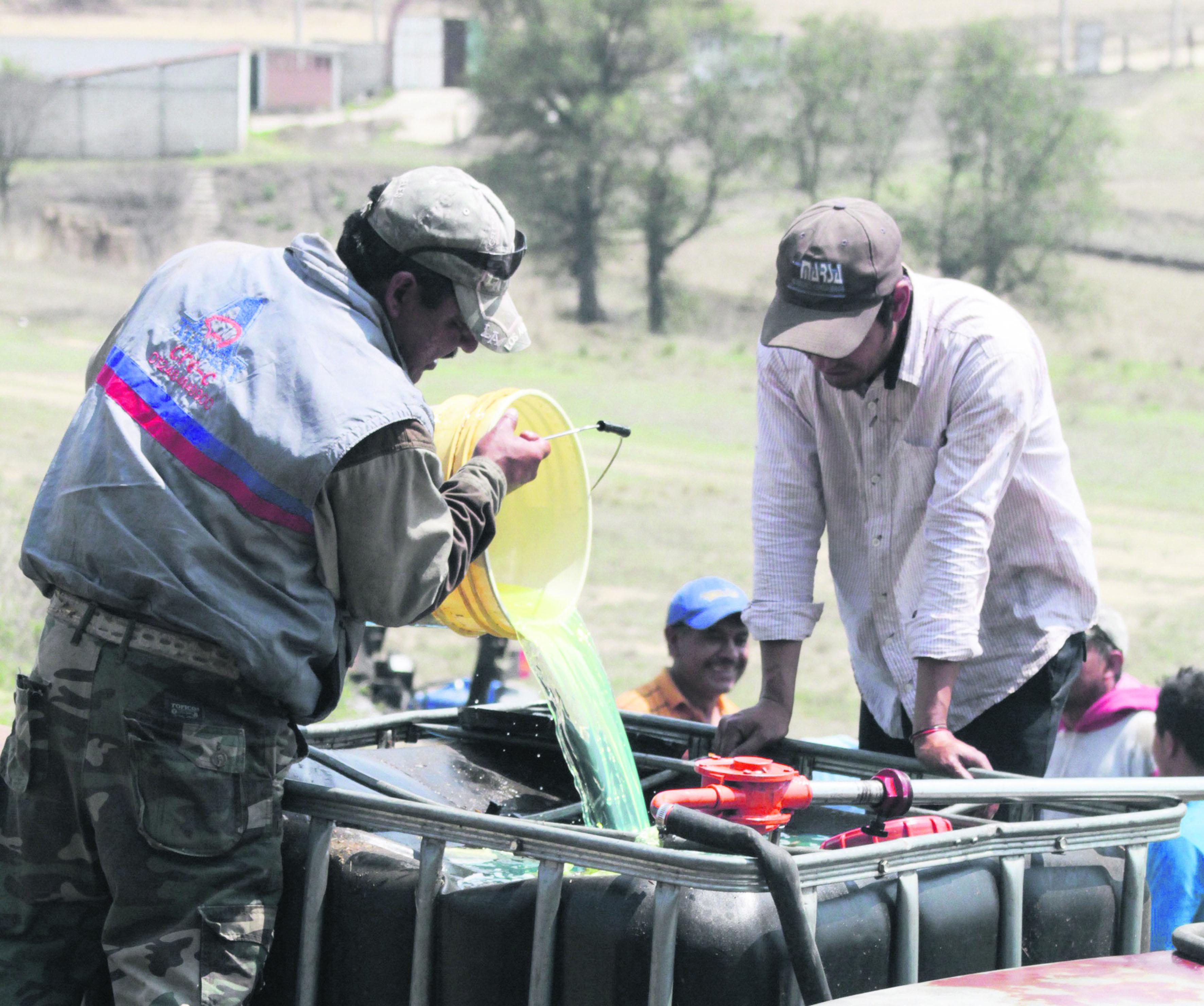 Grupo de personas vertiendo huachicol (combustible robado), en un deposito con capacidad de 1000 litros.