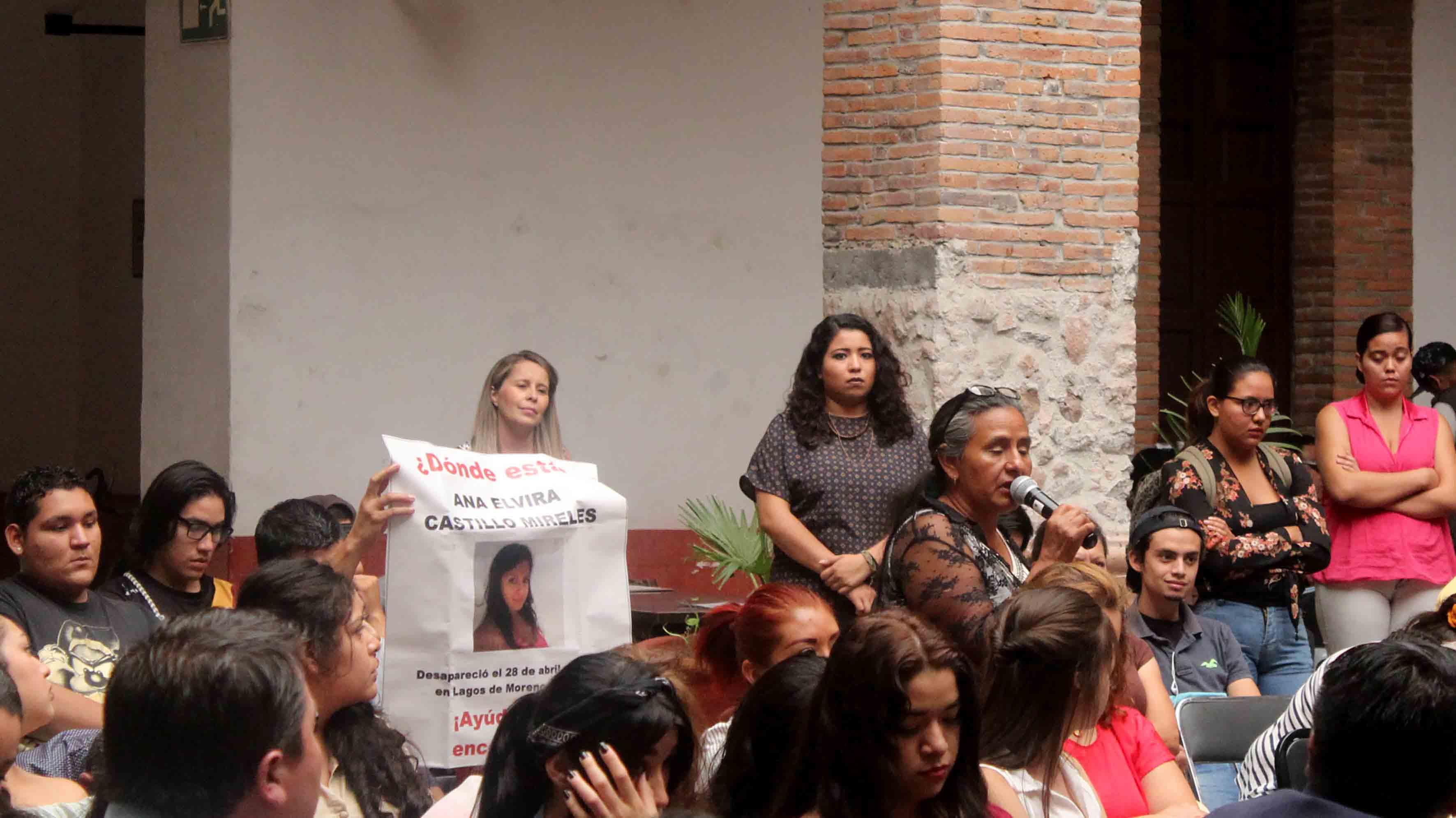 Asistente al seminario, mostrando pancarta con el retrato de una mujer desaparecida.