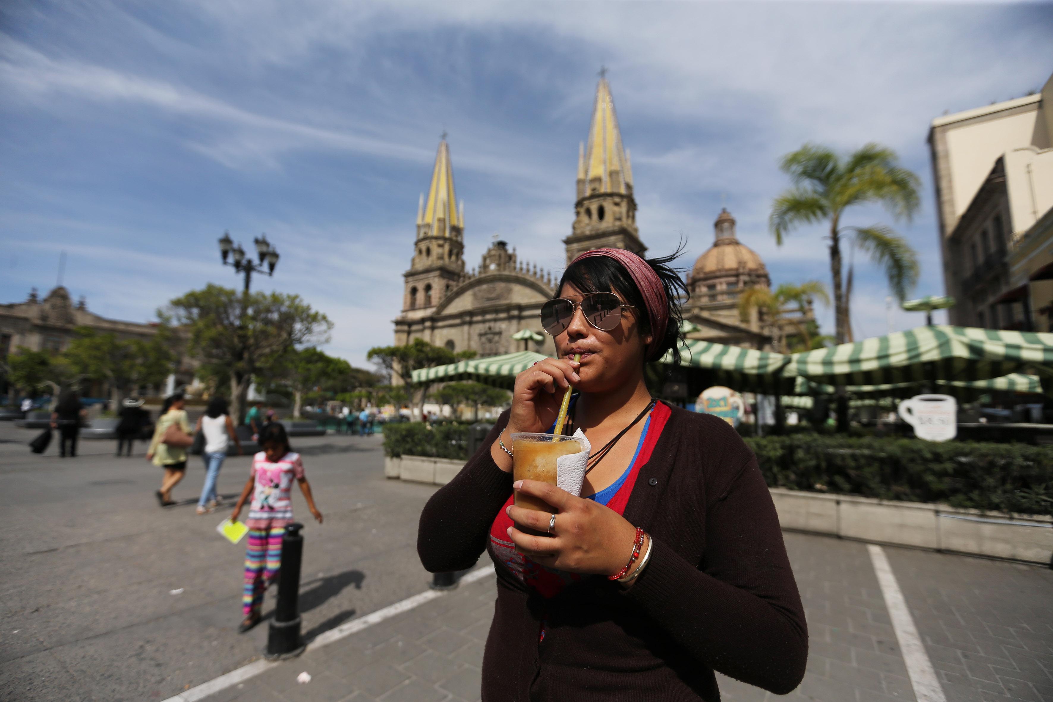 Mujer habitante de la ciudad de Guadalajara, tomando una bebida típica de la región.