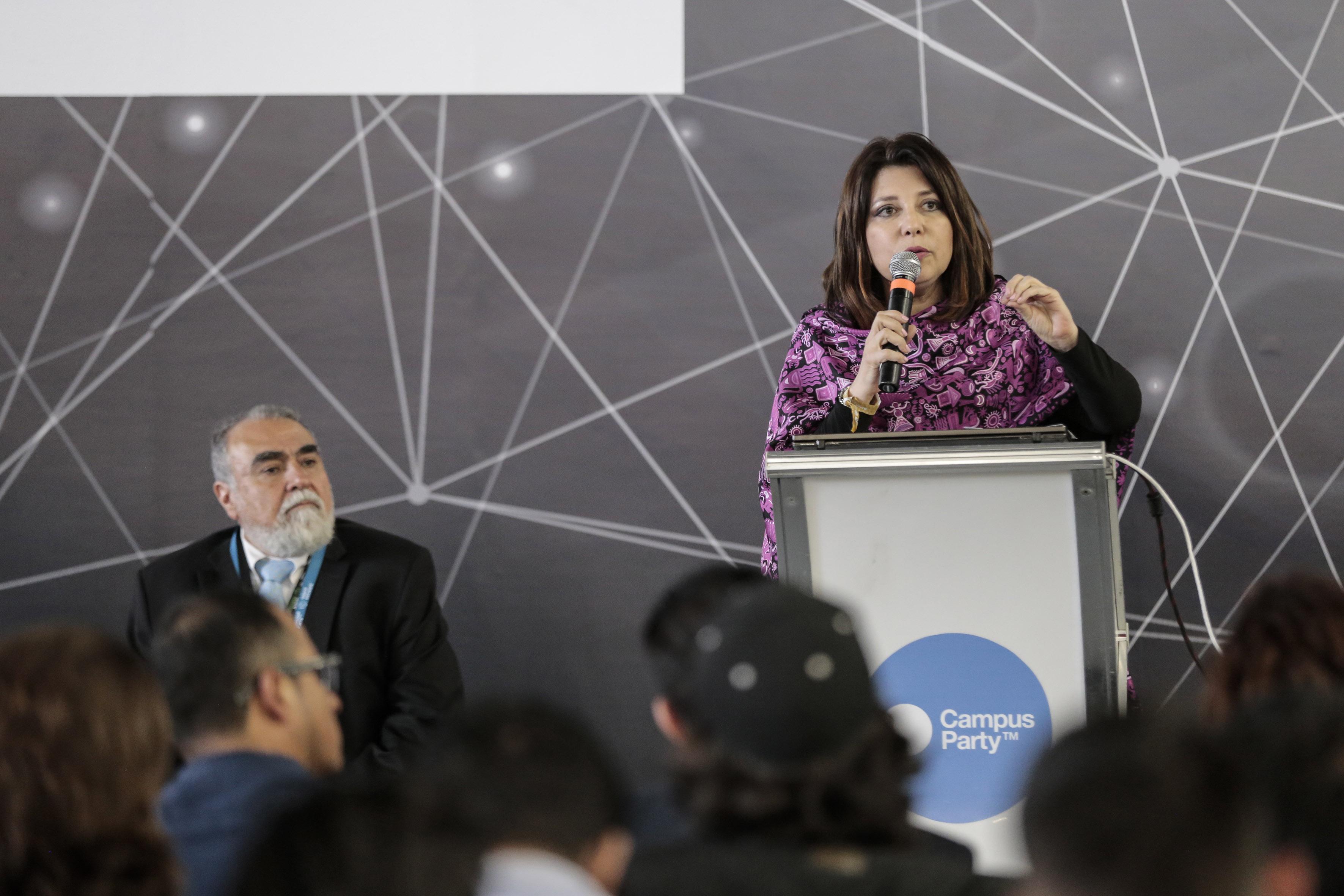 Doctora Carmen Enedina Rodríguez Armenta, Coordinadora General Administrativa,  en podium del evento y con micrófono en mano, haciendo uso de la palabra.