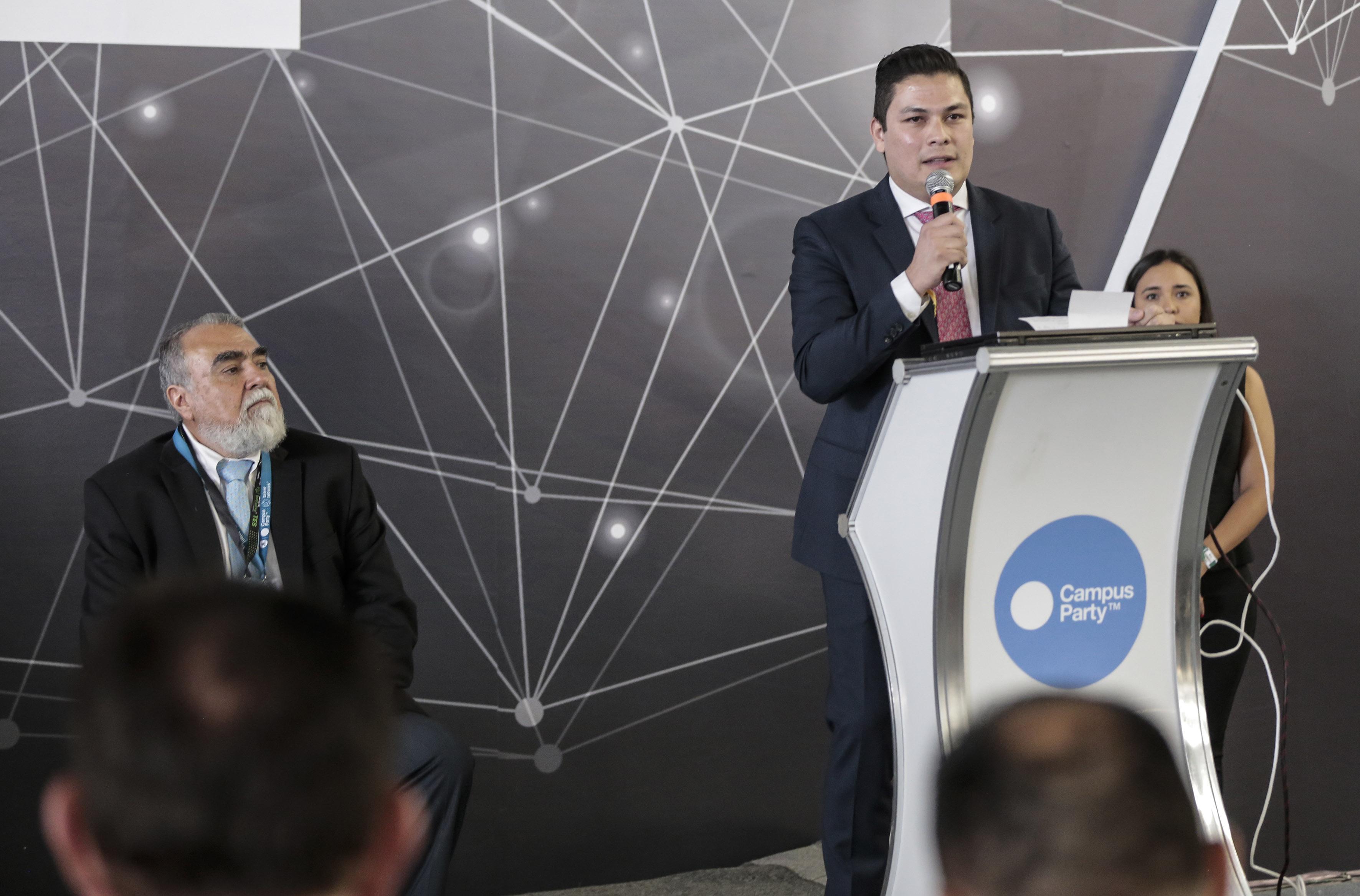 Ing. José Alfonso Fonseca García, Director General de Innovación y Gobierno Digital, en podium del evento y con micrófono en mano, haciendo uso de la palabra.
