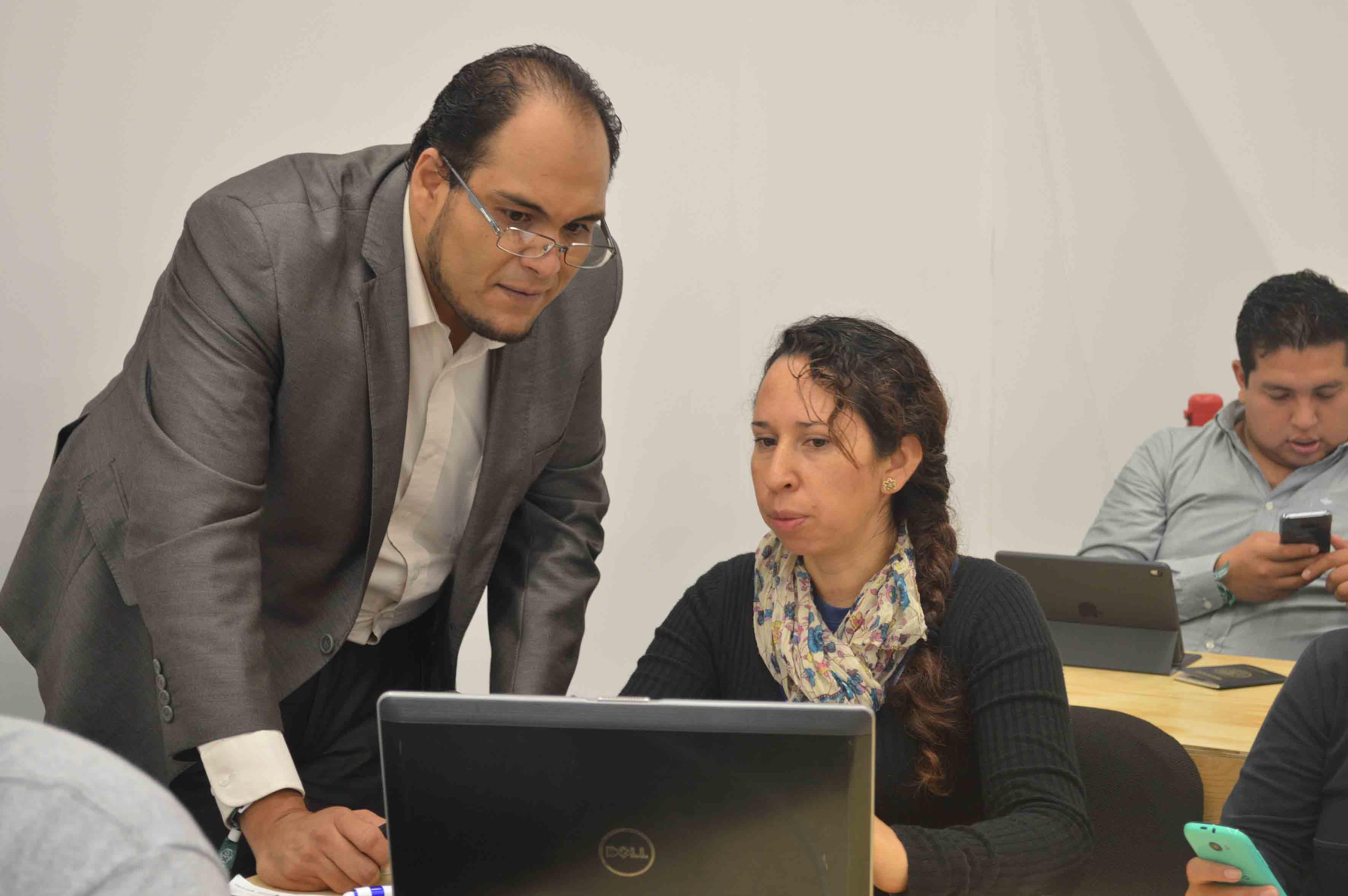 Doctor Rigoberto Franco Vizcarra, asesor de UDGVirtual, interactuando con joven asistente al taller.