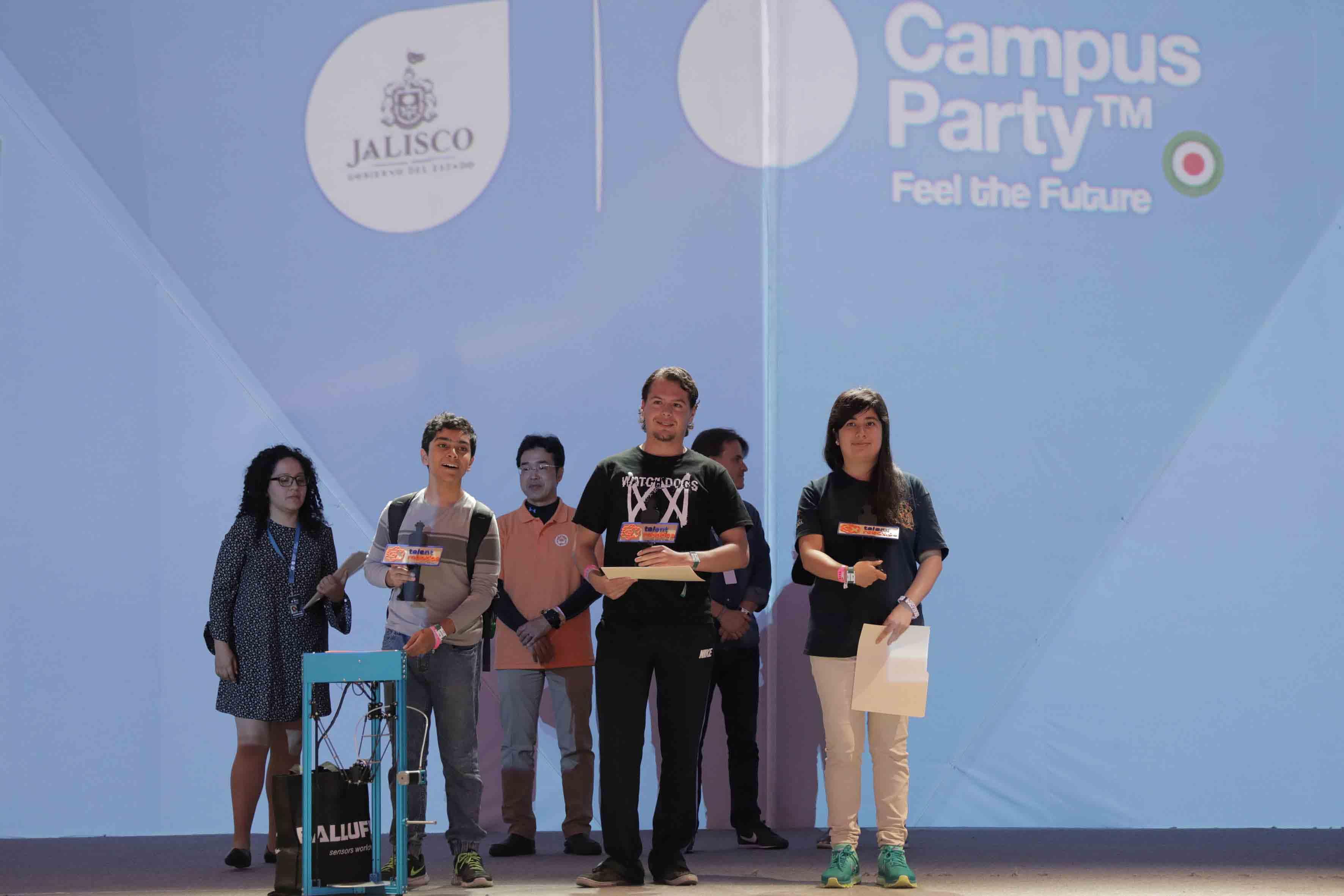 Estudiantes becados por la Universidad de Guadalajara, mostrando sus galardones, frente al público asistente.