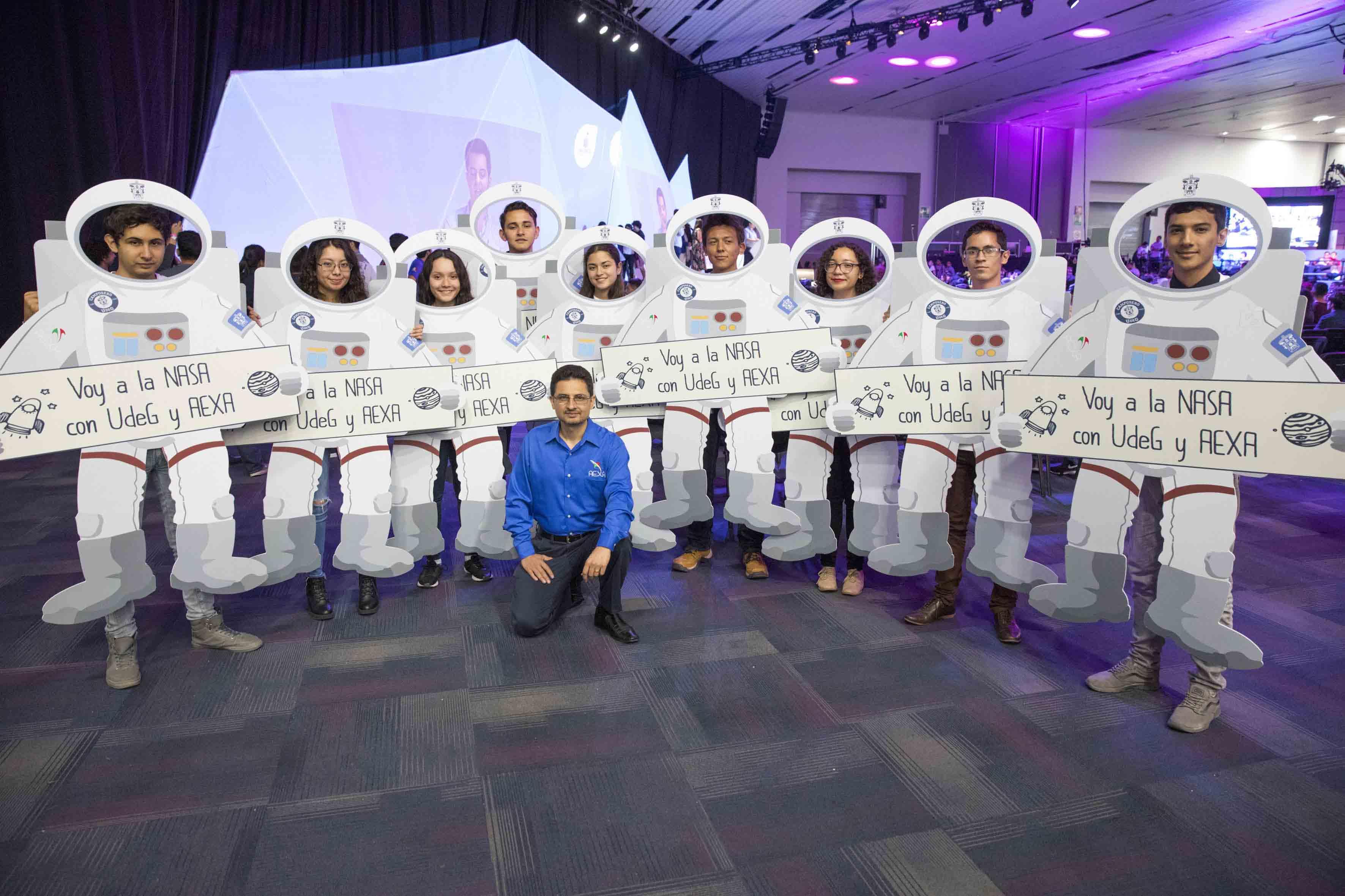 Estudiantes de la Universidad de Guadalajara y ganadores de ambos retos, posando con un traje espacial de cartón, para la fotografía grupal.