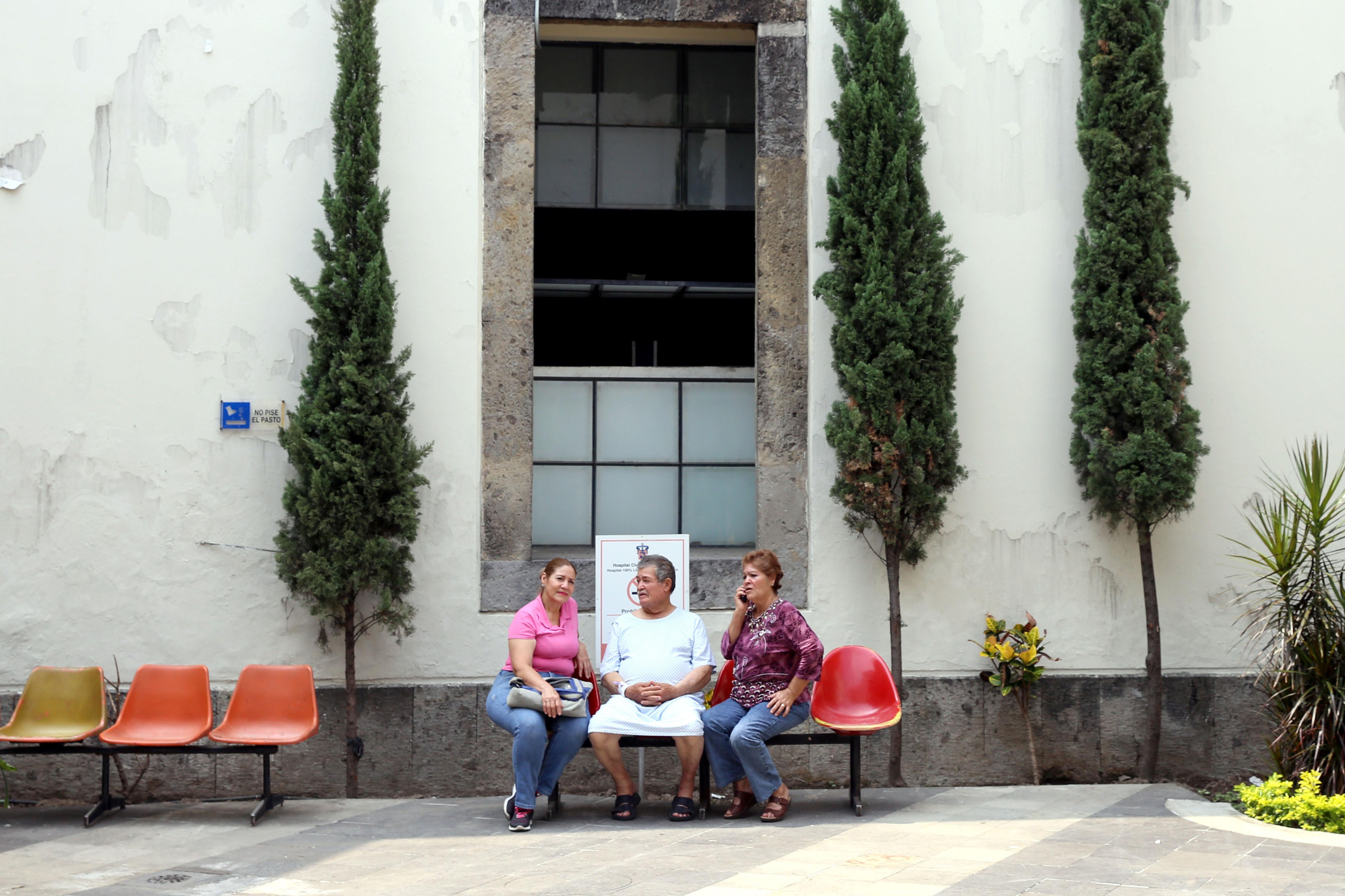 Paciente del Hospital Civil de Guadalajara, sentado en el patio del mismo y en compañía de dos miembros de su familia.