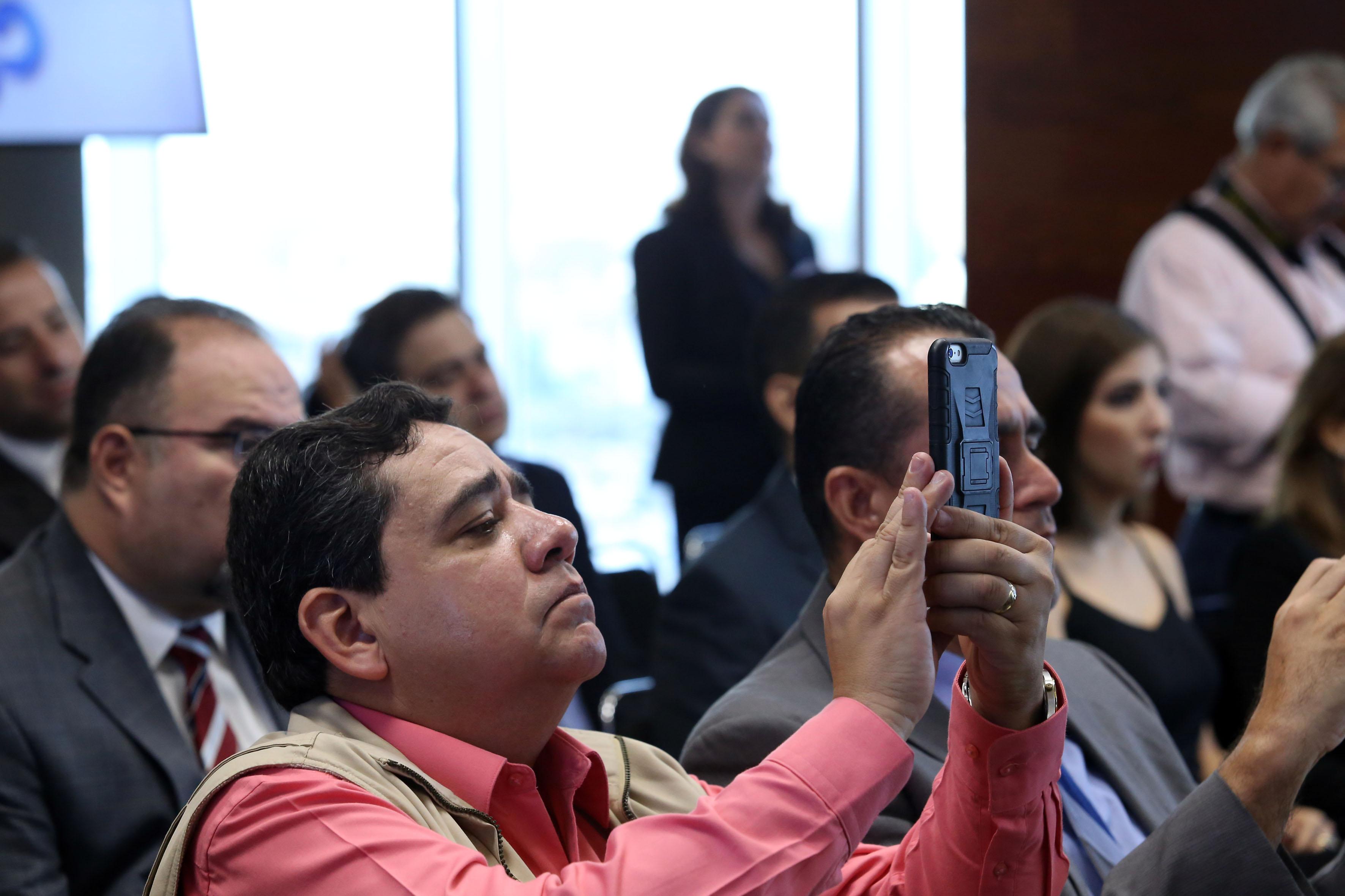 Asistente a la conferencia, tomando fotografías con su teléfono celular.