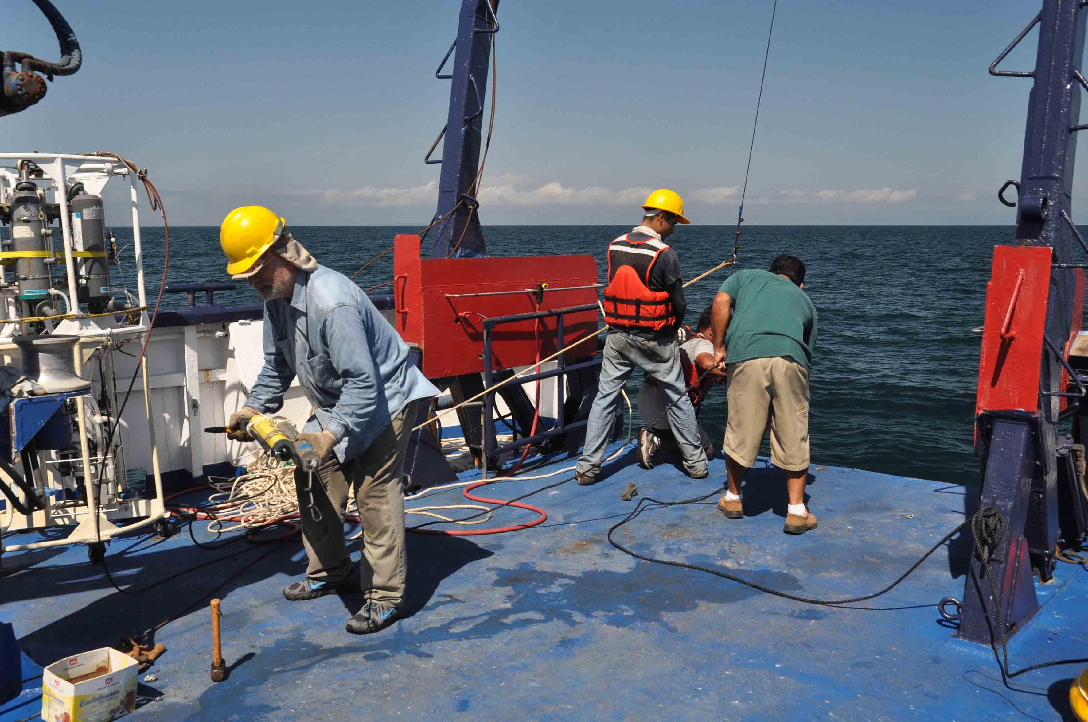Investigadores y equipos de apoyo, en plataforma de un barco bajando un liberador acústico hacia al océano para su estudio.