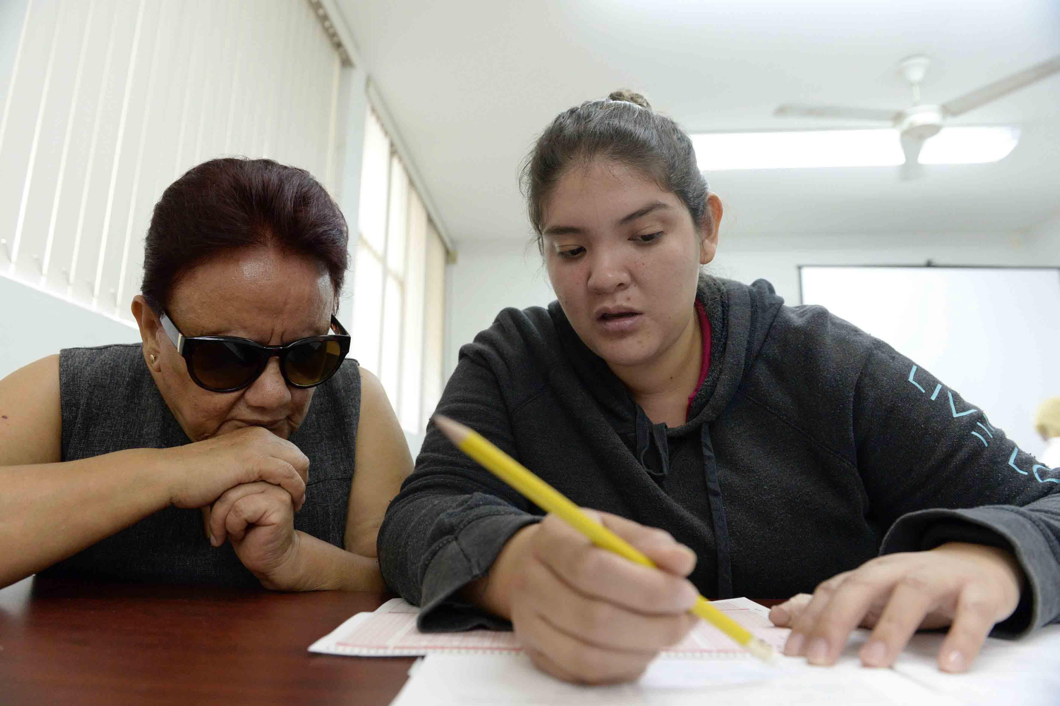 Bibliotecaria fungiendo como lector intérprete, a estudiante con Discapacidad Visual, en la presentación de su examen.