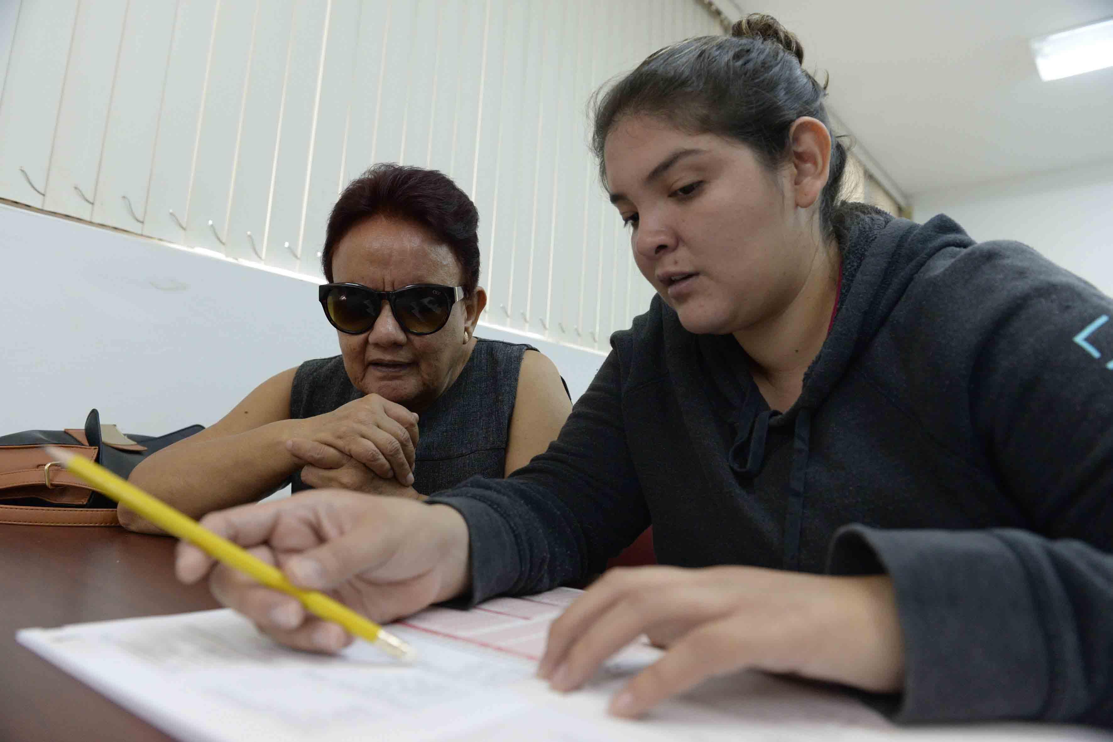 Personal de la Biblioteca, fungiendo como lector intérprete en la realización de exámenes, para personas con Discapacidad Visual.