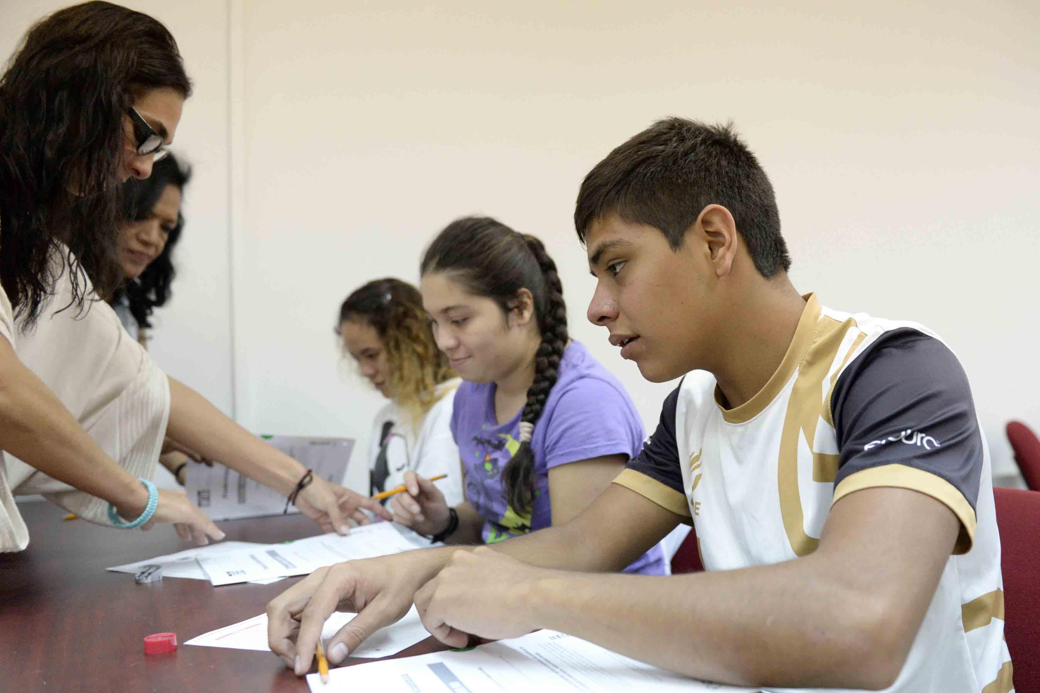 Miembros del área de Servicios Bibliotecarios, fungiendo como lectores intérpretes para personas con Discapacidad Visual, en la realización de sus exámenes escritos.