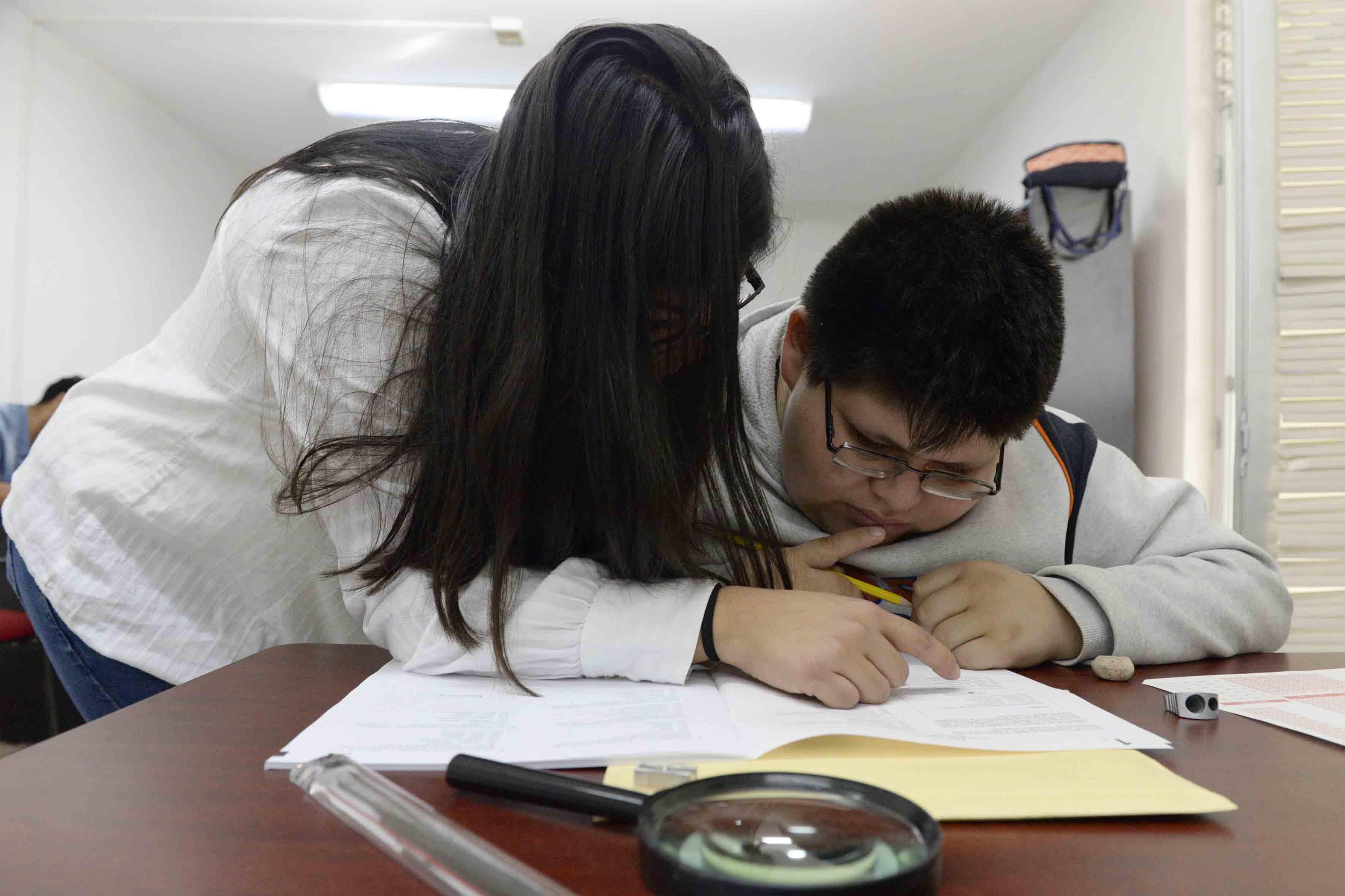 Estudiante con Discapacidad Visual realizando examen escrito, mediante la interpretación de un lector profesional.