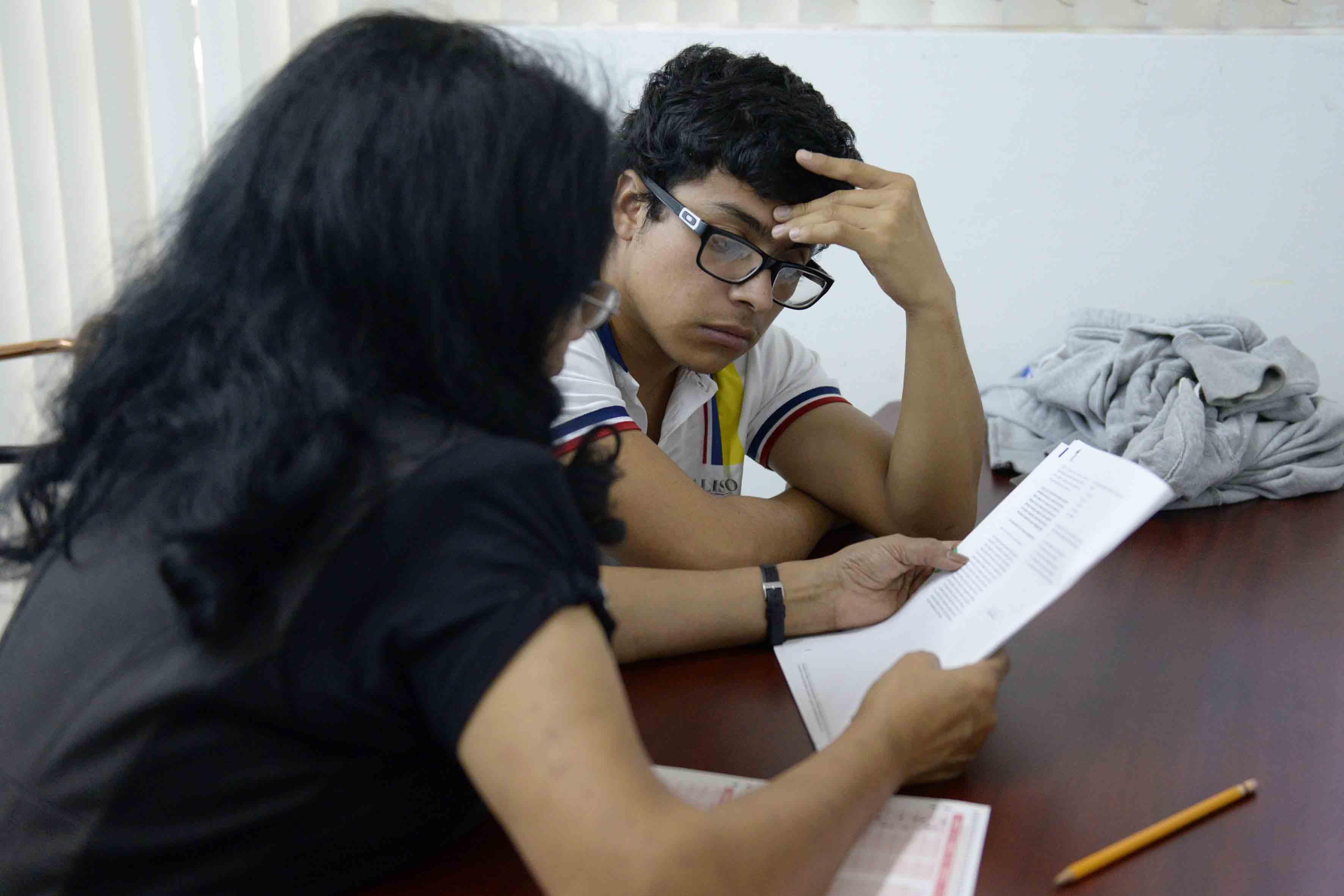 Estudiante con Discapacidad Visual realizando examen escrito, con el apoyo de un lector.