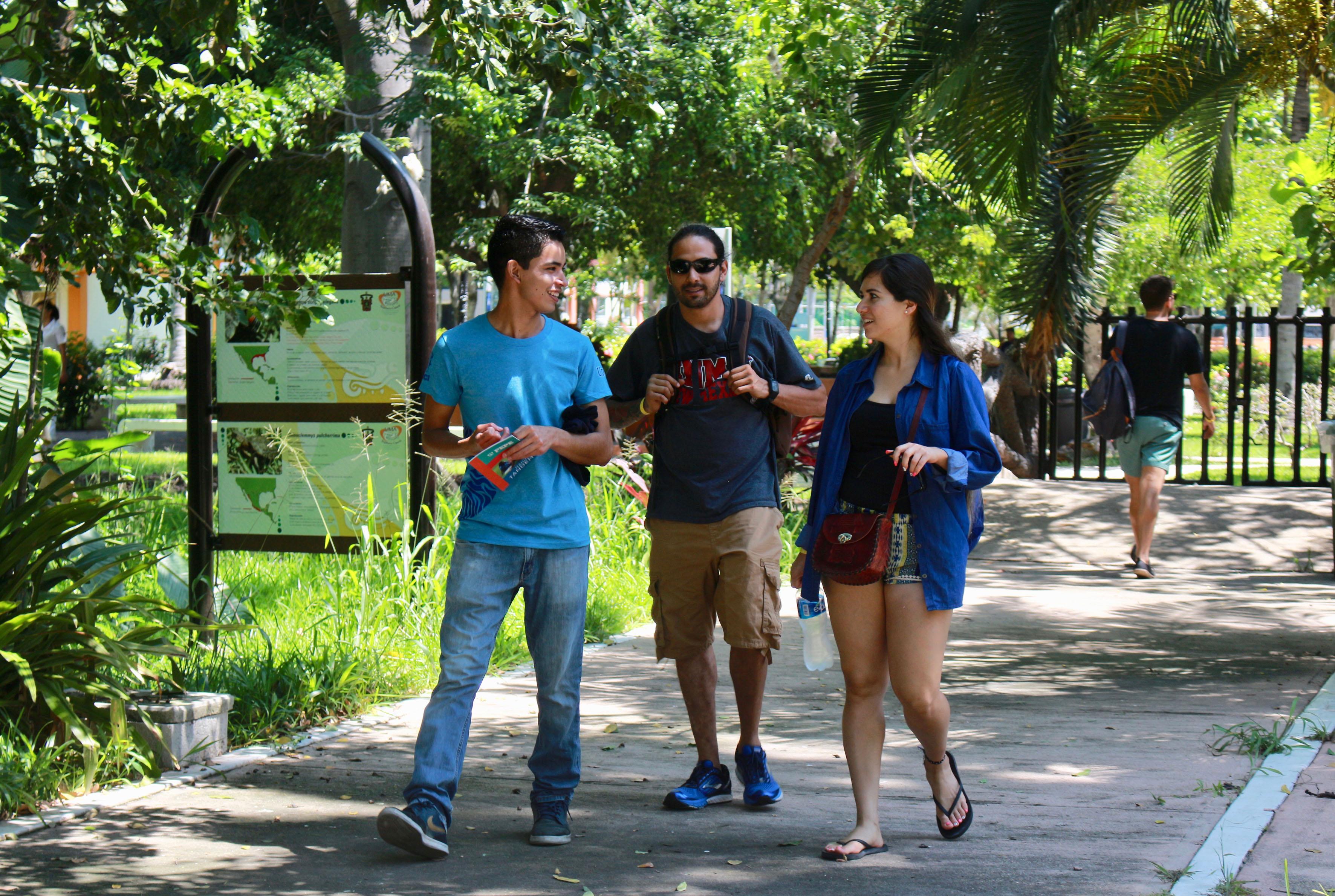 Estudiantes del programa de español para extranjeros del CUCosta, pasando por uno de los pasillos de los exteriores del centro universitario