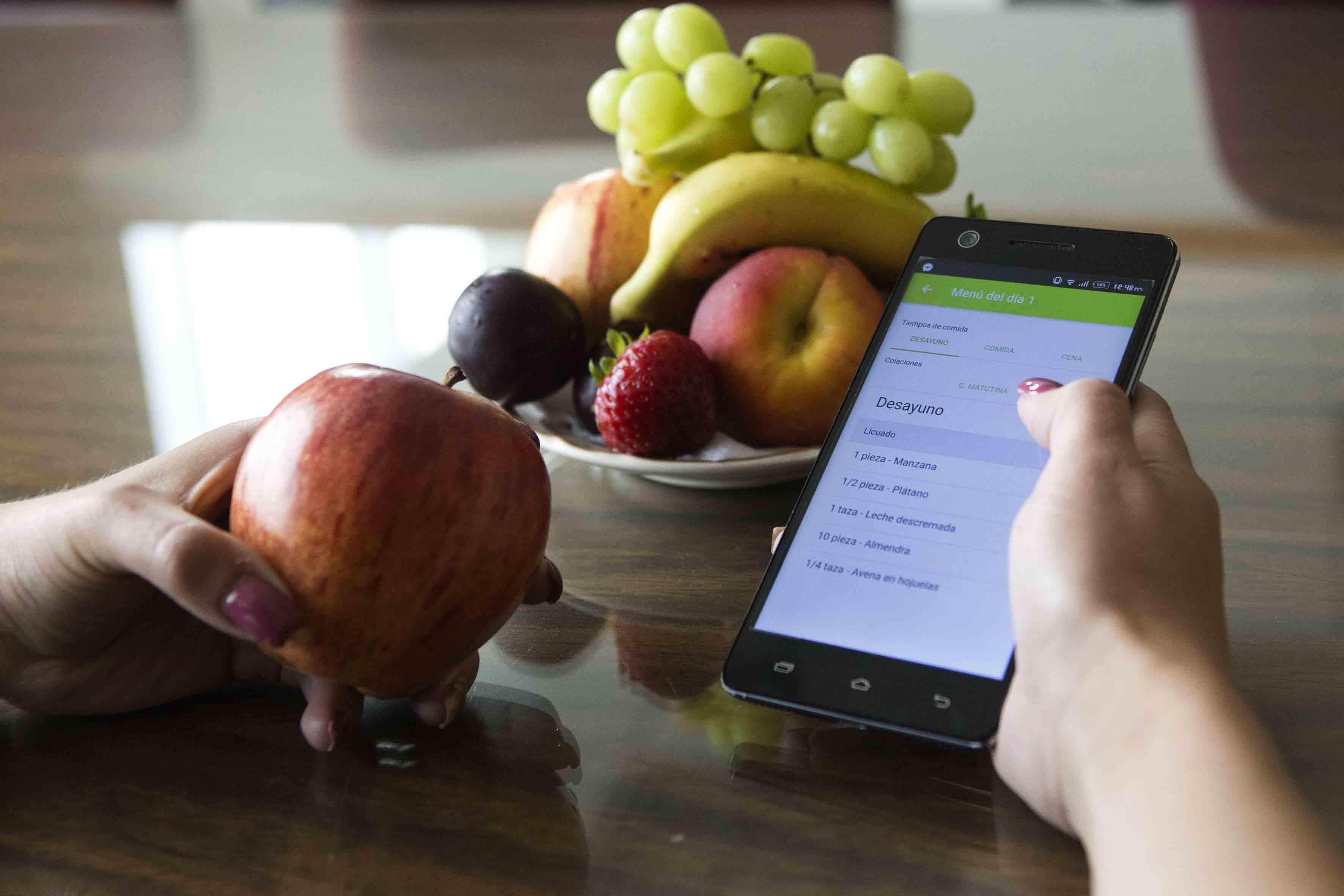Femenina sentada frente a plato de frutas, sosteniendo una manzana con una mano, mientras con la otra maneja una aplicación de nutrición con su celular.