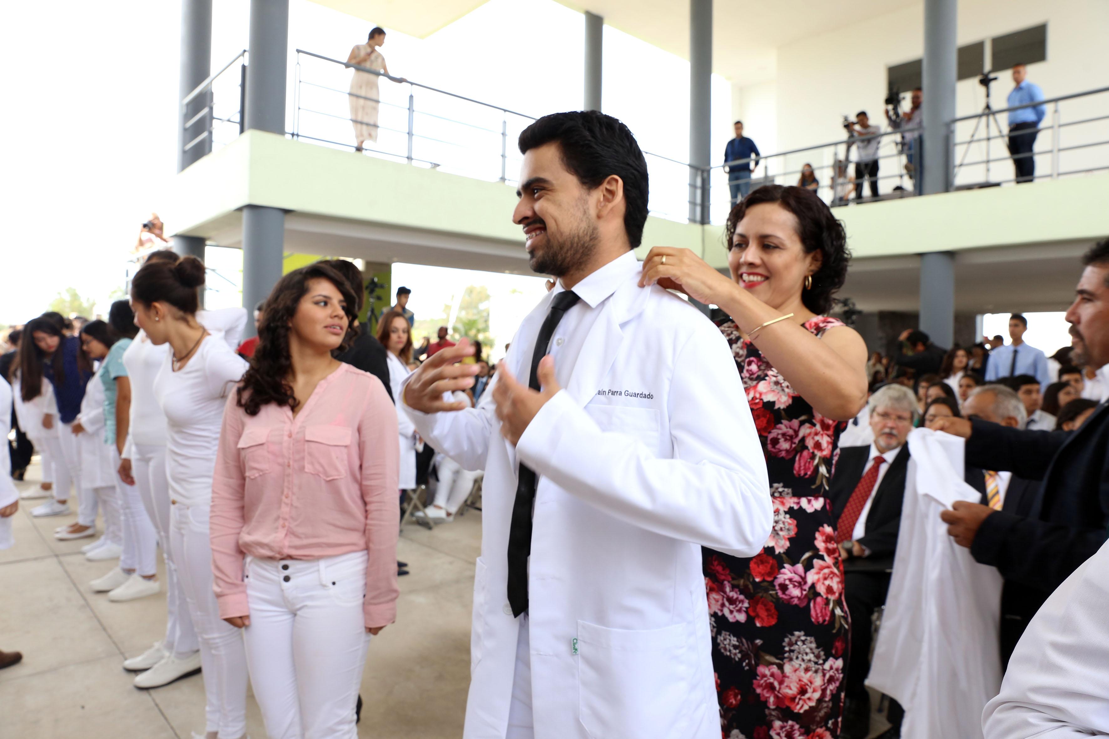 Estudiantes de medicina recibiendo bata por parte de su madre