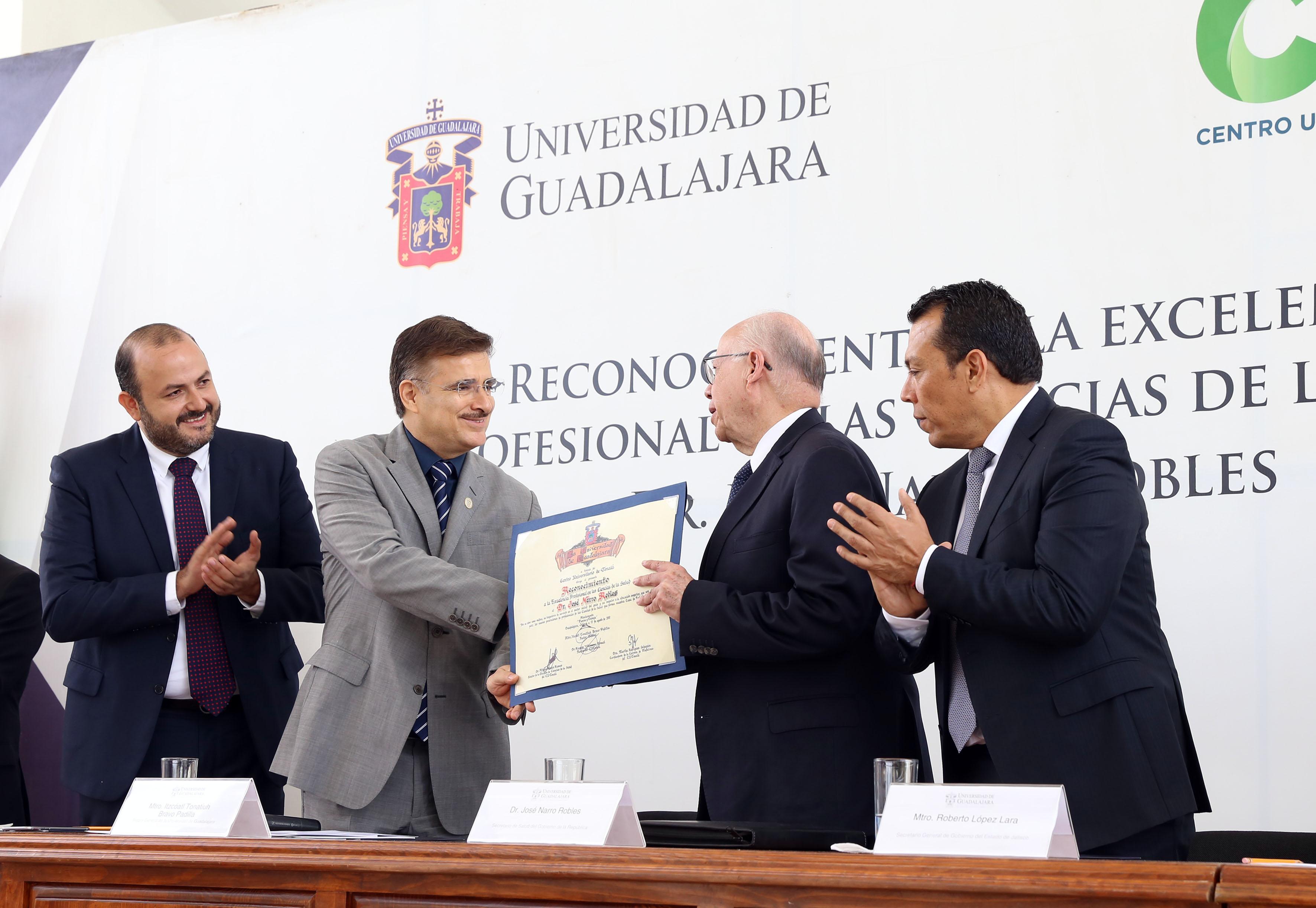 José Narro Robles, Secretario de Salud federal, recibiendo  el Reconocimiento a la Excelencia Profesional en las Ciencias de la Salud, de manos del Rector General de la Universidad de Guadalajara (UdeG), maestro Itzcóatl Tonatiuh Bravo Padilla.