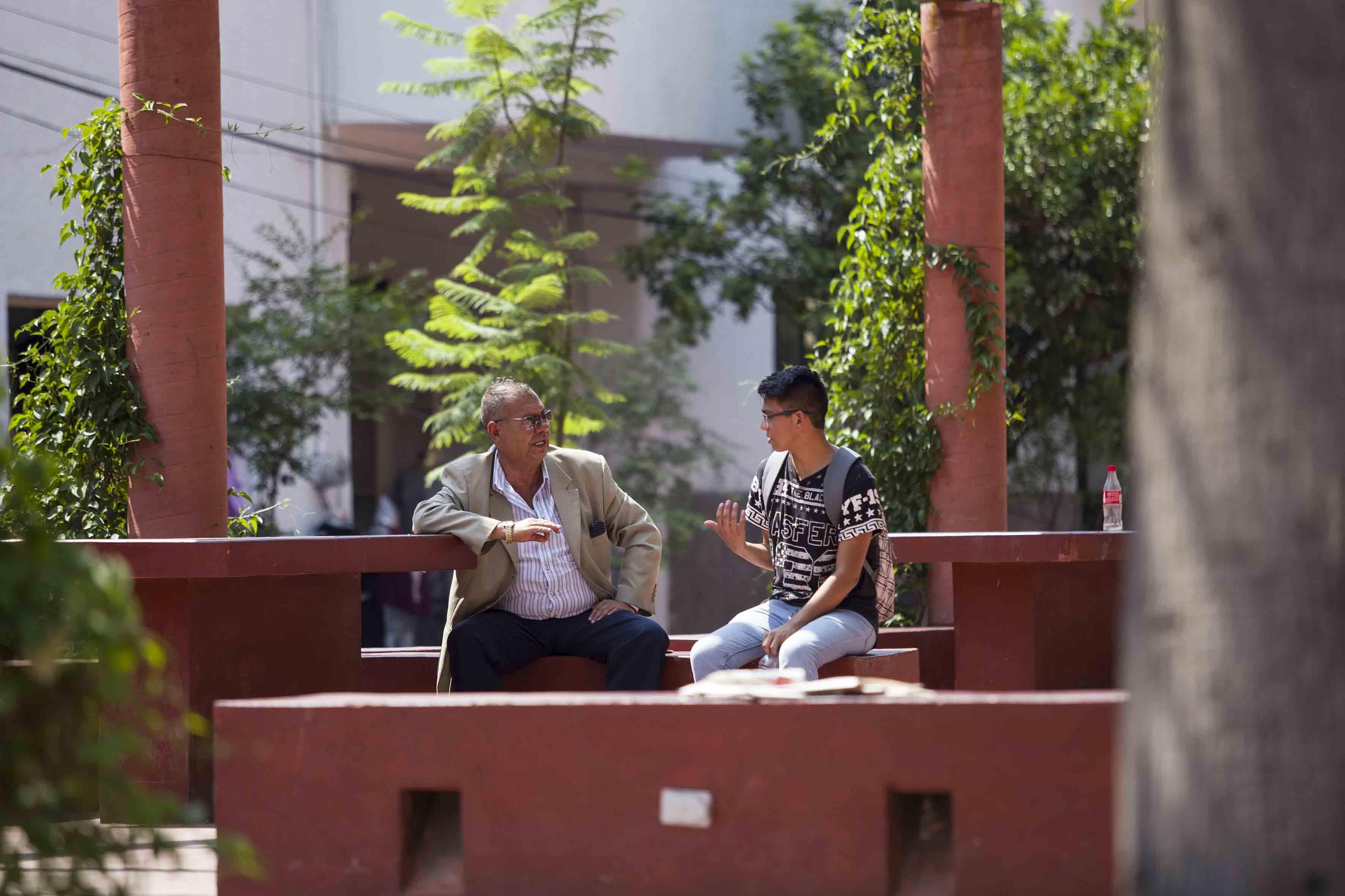 Alumno platicando con su profesor