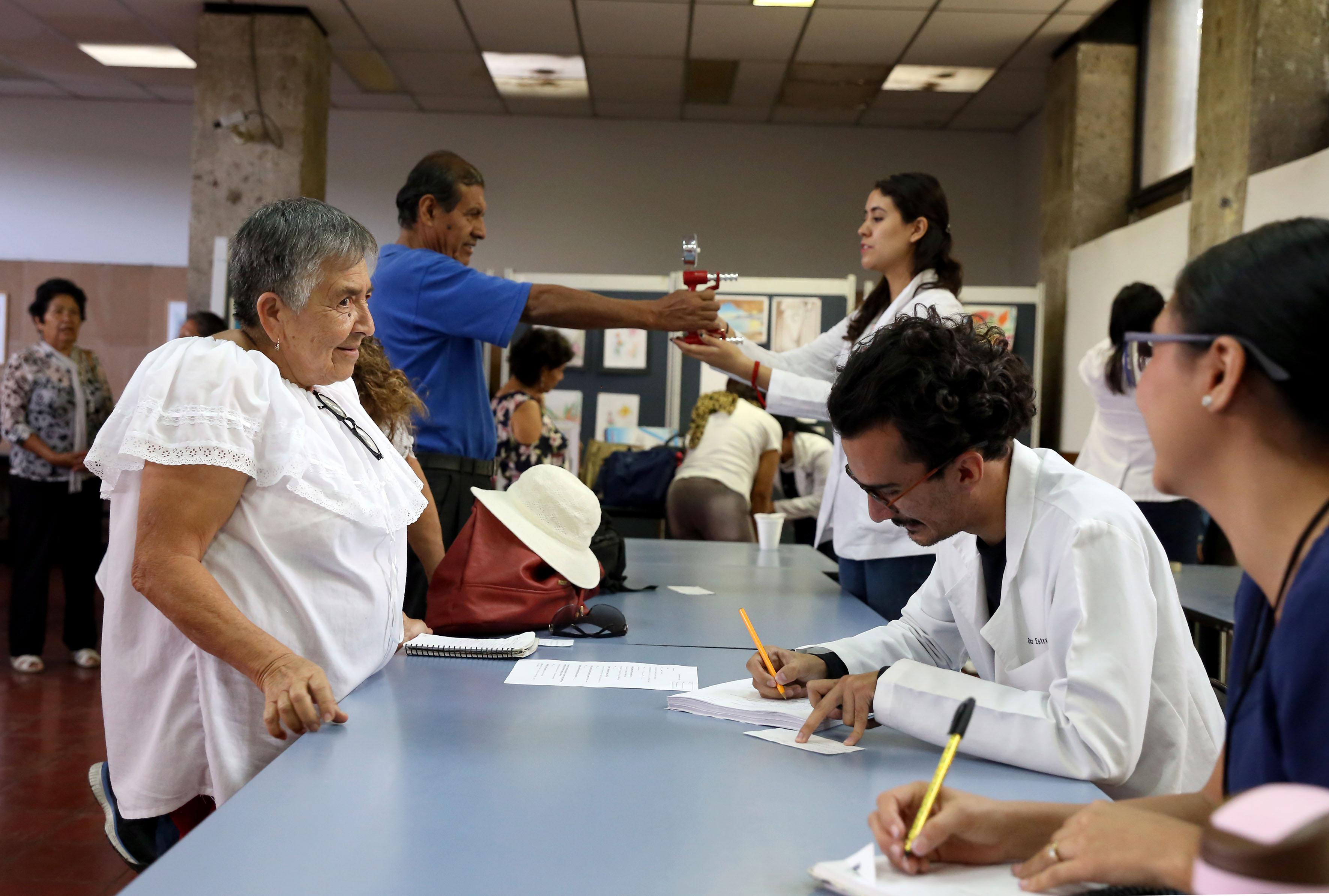 Mesa de registro de adultos mayores a cursos en diferentes áreas del conocimiento, llevada a cabo por personal del SUAM.