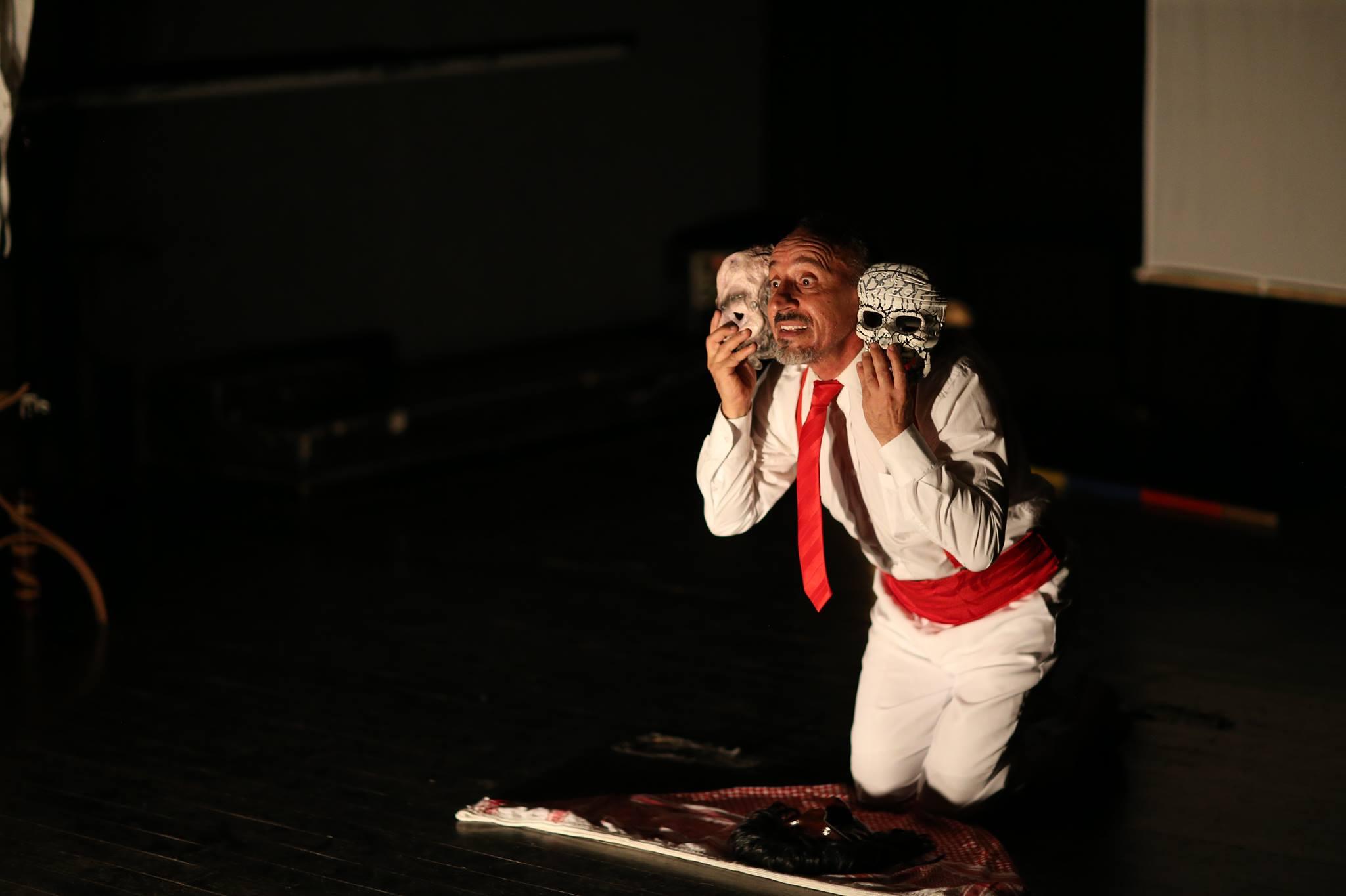 Actor en escena interpretando un personaje. En el que el actor se encuentra hincado con una expresión entre asombro y felicidad, sujetando dos máscaras, una diferente a la otra y colocadas a los lados de su cara.
