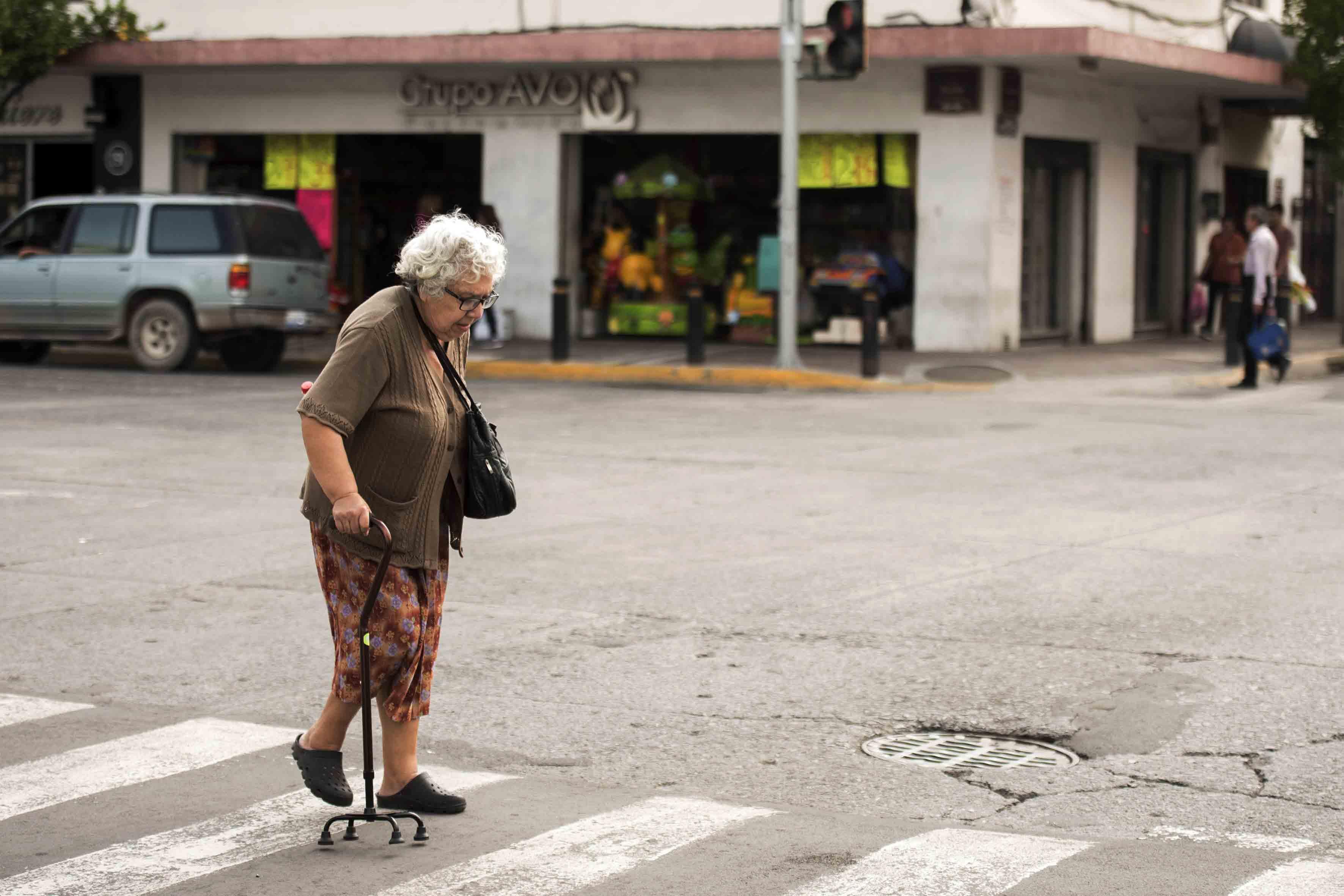 Mujer de la tecera edad, usando bastón de tripie, cruzando una de las calles de la ciudad, donde se observan las grietas, alcantarilla y bache de la calle.