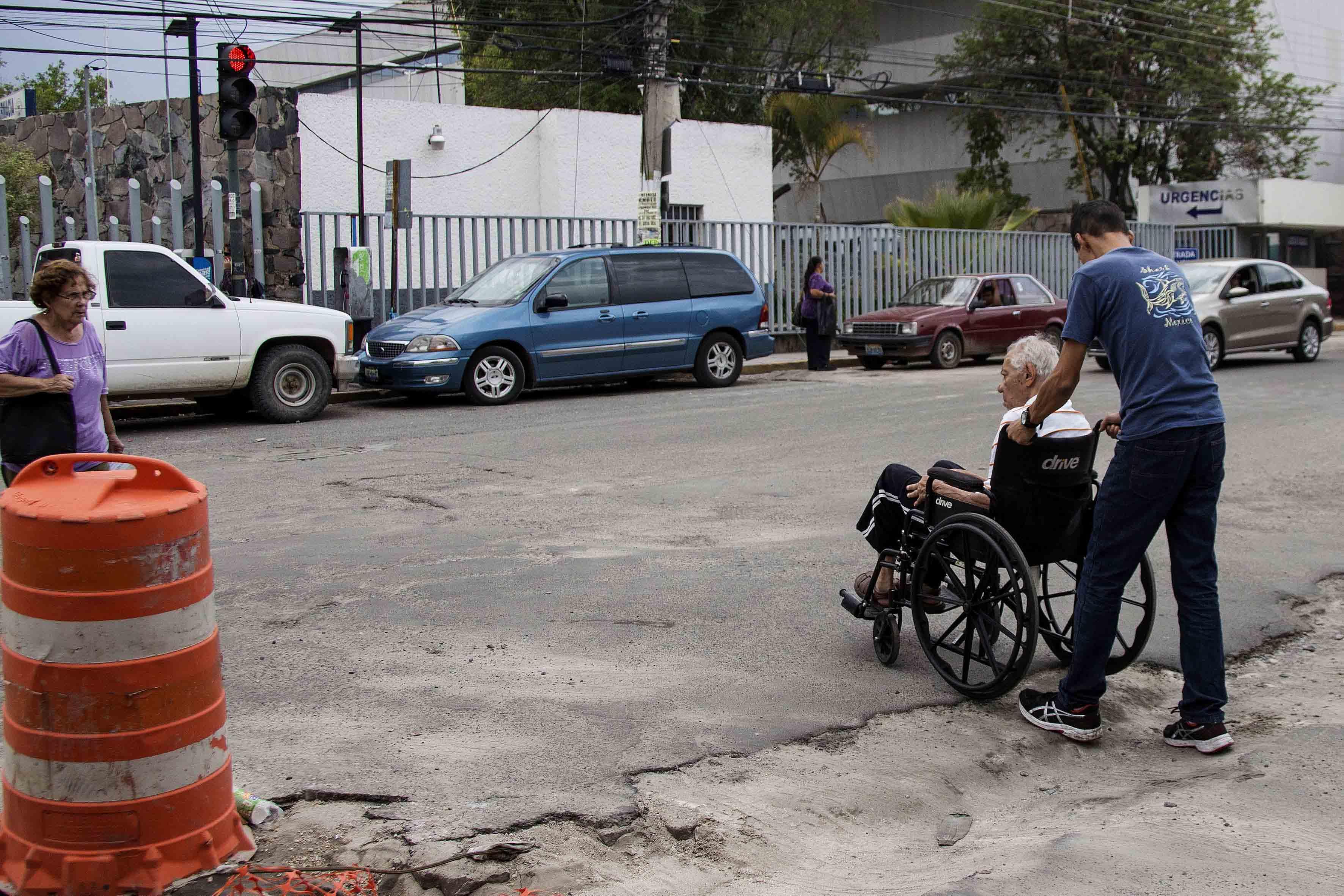 Hombre de la tercera edad en silla de ruedas, tratando de cruzar con la ayuda de un jóven, una de las calles de la ciudad con baches para llegar a un hospital.