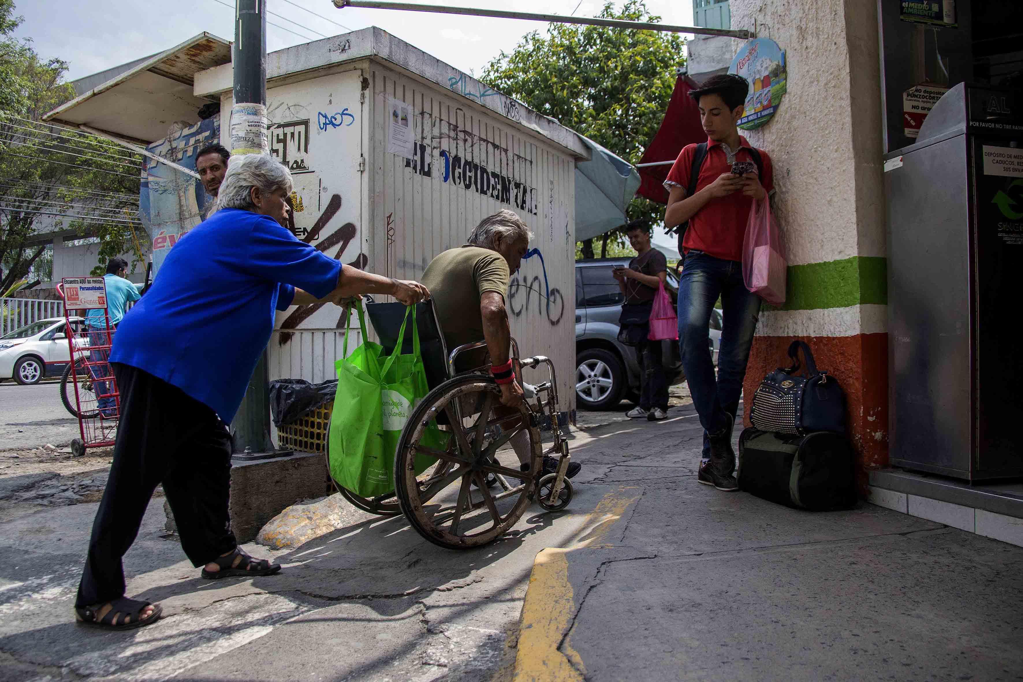 Hombre de la tercera edad, en silla de ruedas tratando de subir por la rampa de una banqueta en estado deporable, con la ayuda de su pareja, también de la tercera edad.